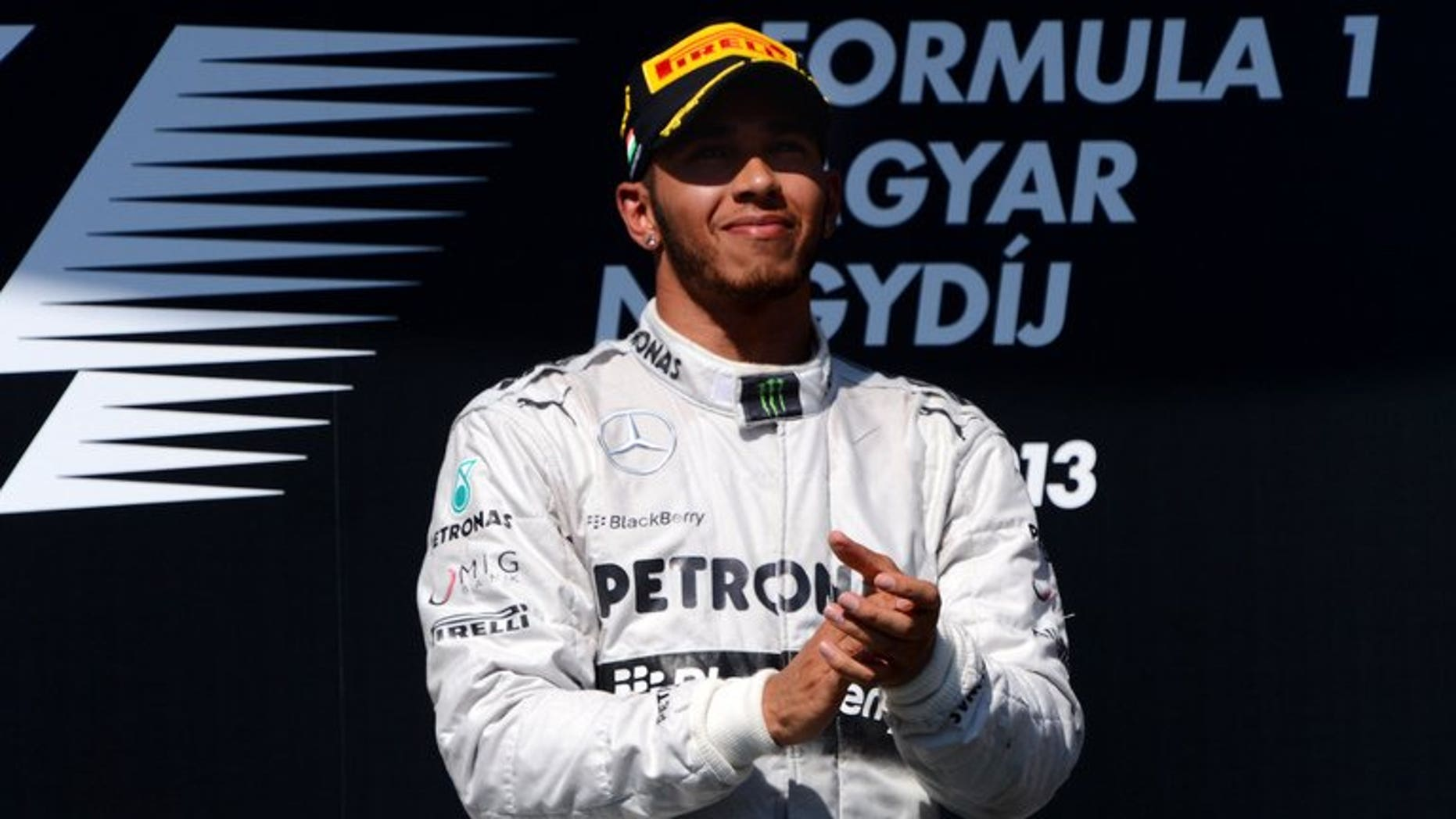 Mercedes' British driver Lewis Hamilton celebrates on the podium at the Hungaroring circuit in Budapest on July 28, 2013. Hamilton's faith in Mercedes was repaid by a victory that will give him the momentum to mount a title bid in the second half of the Formula One season, according to team chief Ross Brawn.