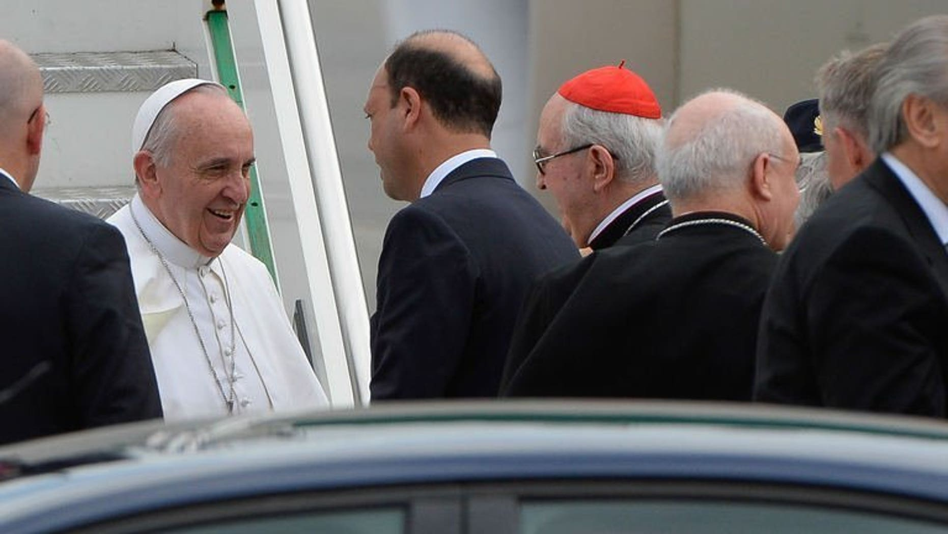 Pope Francis (L) speaks with Italian interior minister and deputy premier Angelino Alfano (C) after disembarking from his plane at Rome's Ciampino international airport on July 29, 2013. Pope Francis on Monday condemned the gay lobby but said that homosexuals should not be marginalised.