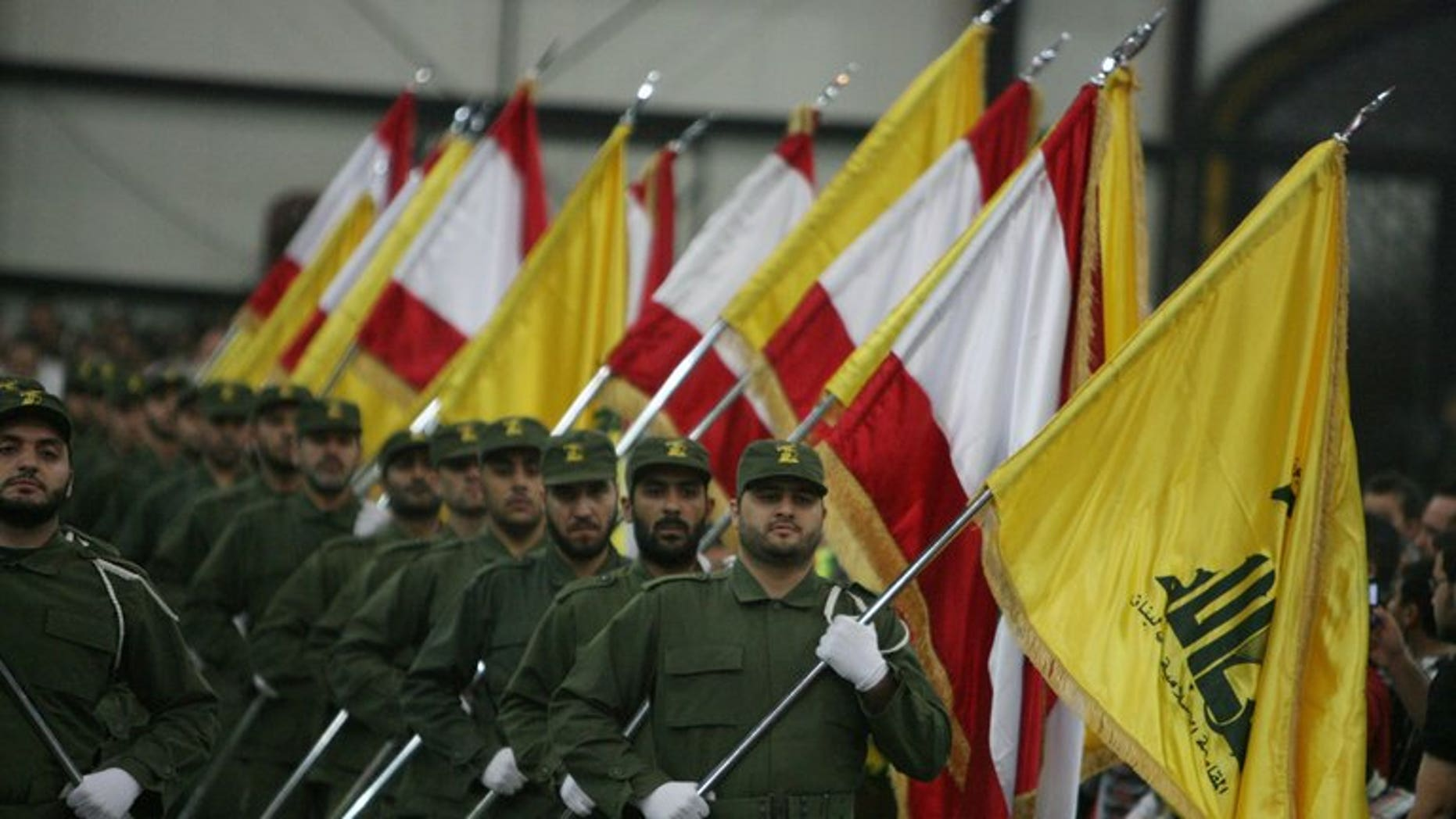 Hezbollah fighters hold up Lebanese flags and the yellow flag of the militant Shiite Muslim group in Beirut on November 11, 2009. Nigerian prosecutors on Monday widened charges against three Lebanese nationals accused of links to Hezbollah as their trial began with access to the courtroom restricted and the identities of witnesses concealed.
