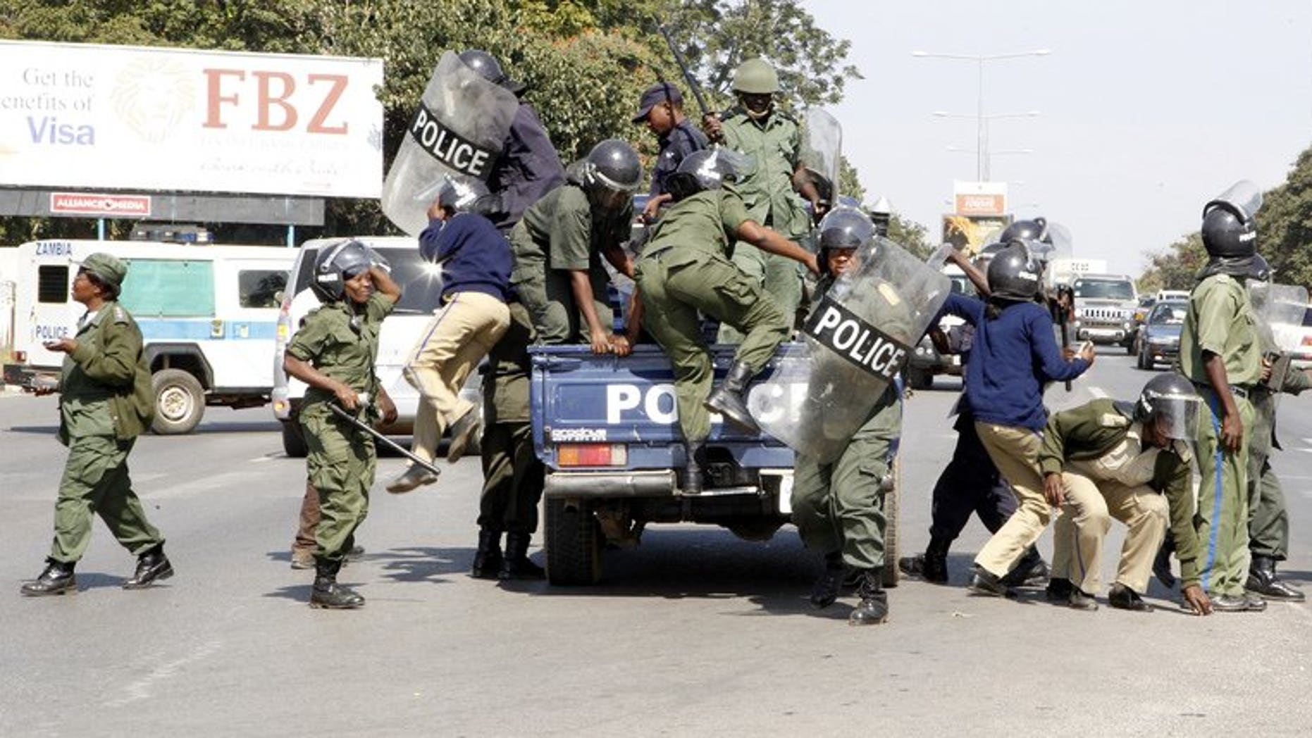 Zambian police officers arrive at the University of Zambia on May 17, 2013 in Lusaka. Zambian police on Monday arrested and charged a journalist with having porn on his computer in another apparent crackdown on a publication critical of the government, his lawyer said.