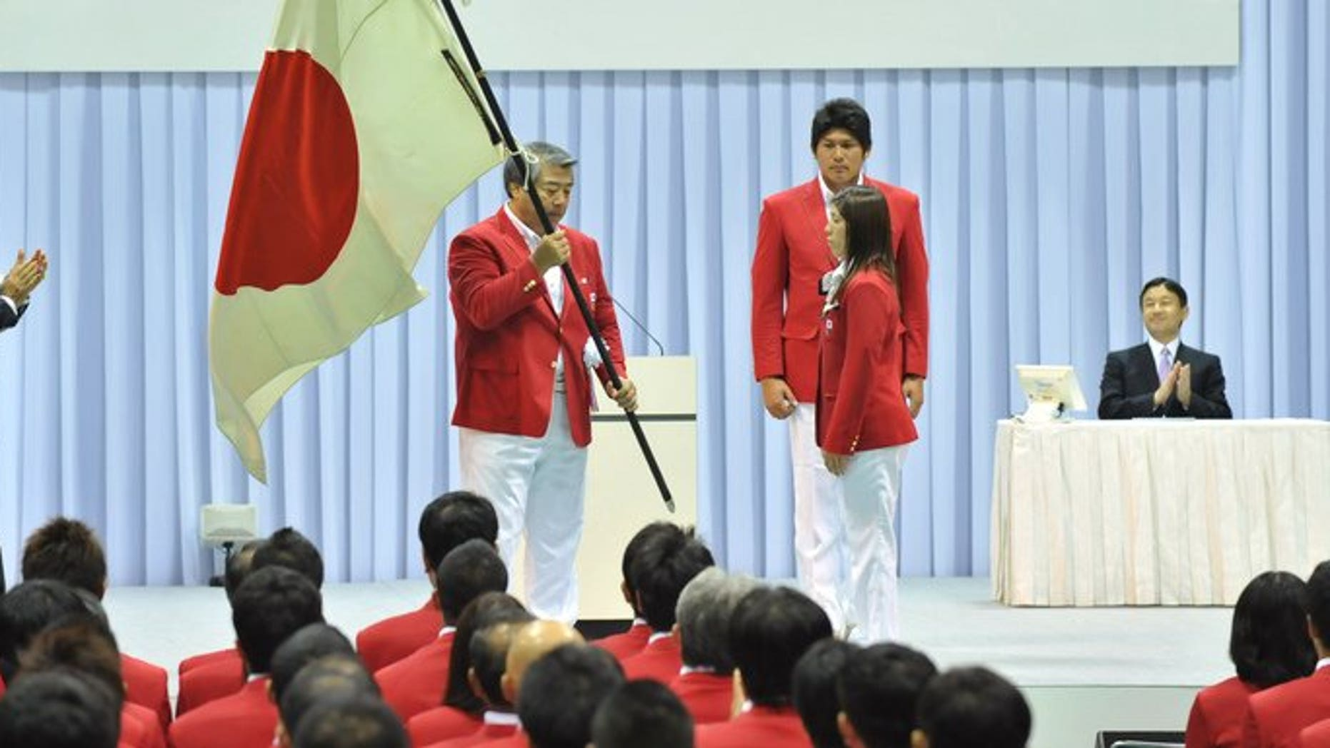 The head of the All Japan Judo Federation Haruki Uemura (C) holds the national flag at a ceremony in Tokyo in 2012. Uemura is to announce his resignation according to reports, after the sport was sullied in its birthplace by a series of scandals including abusive coaching, sexual harassment and misuse of funds.