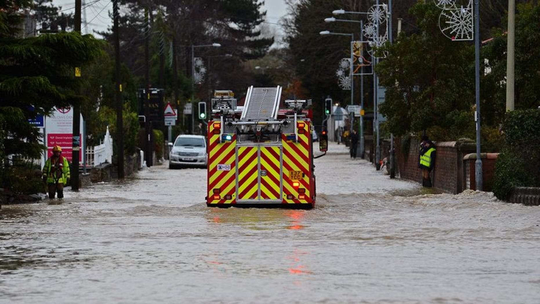 """Fire crews pumped water out of properties in the West Yorkshire town of Todmorden after a """"torrential"""" downpour caused flash floods. File picture for illustration only shows a fire engine moving along a flooded road."""