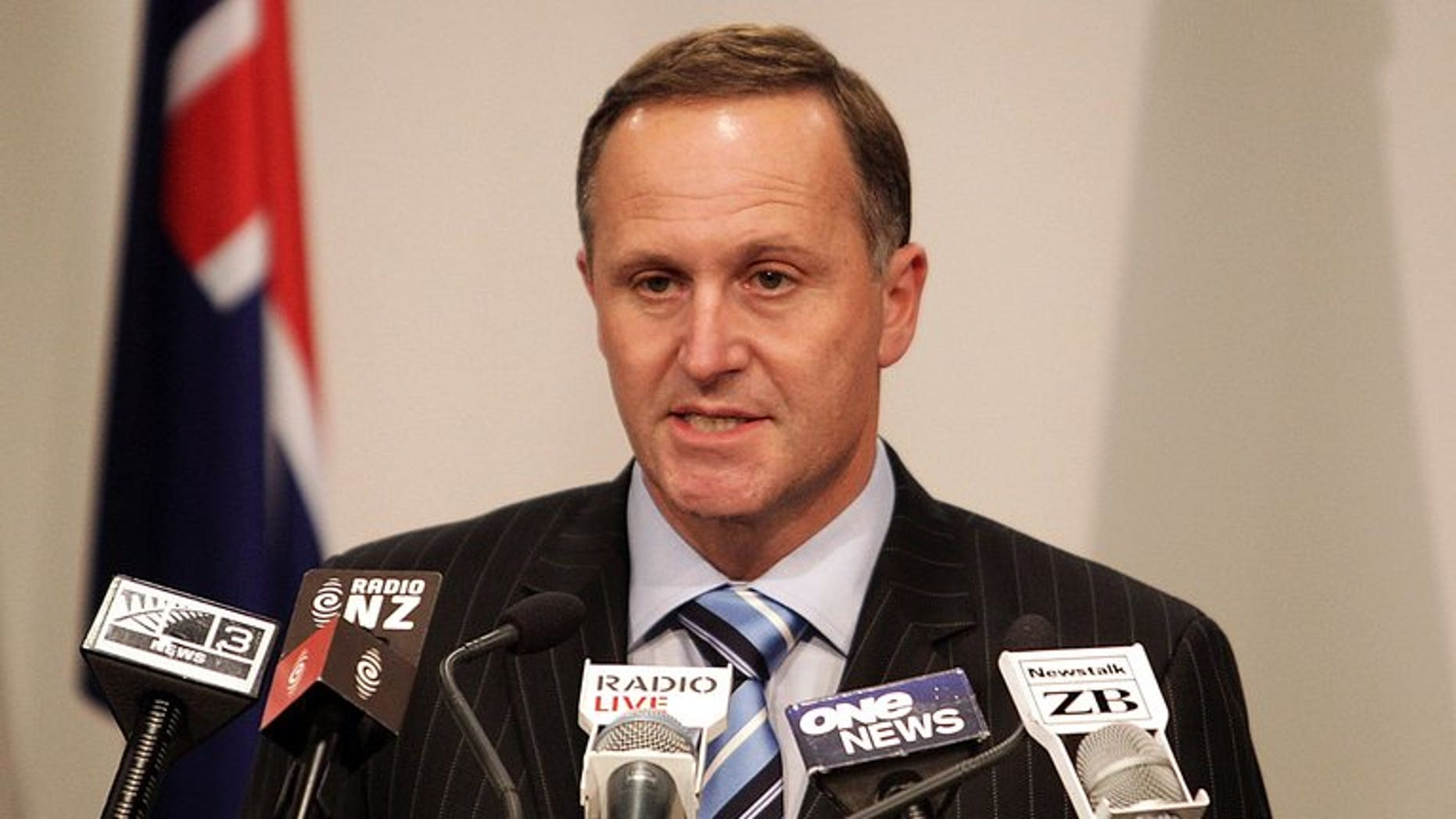 """New Zealand's Prime Minister John Key speaks to the media in Wellington on October 27, 2010. The """"hacktivist"""" group Anonymous briefly crashed Key's website in protest at plans to allow the country's intelligence agency to spy on local residents."""
