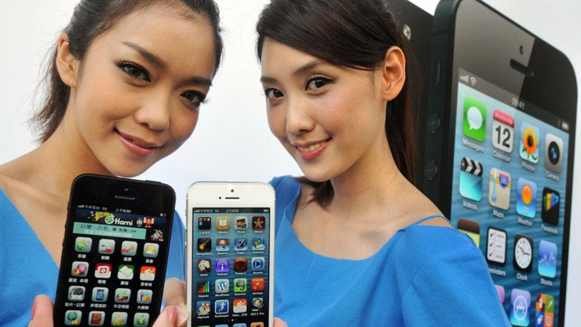Women hold the Apple iPhone 5 during a launch at a store in Taipei last December. A Taiwanese company which assembles some Apple devices said Tuesday it is investigating claims of labour abuses by a US rights group.