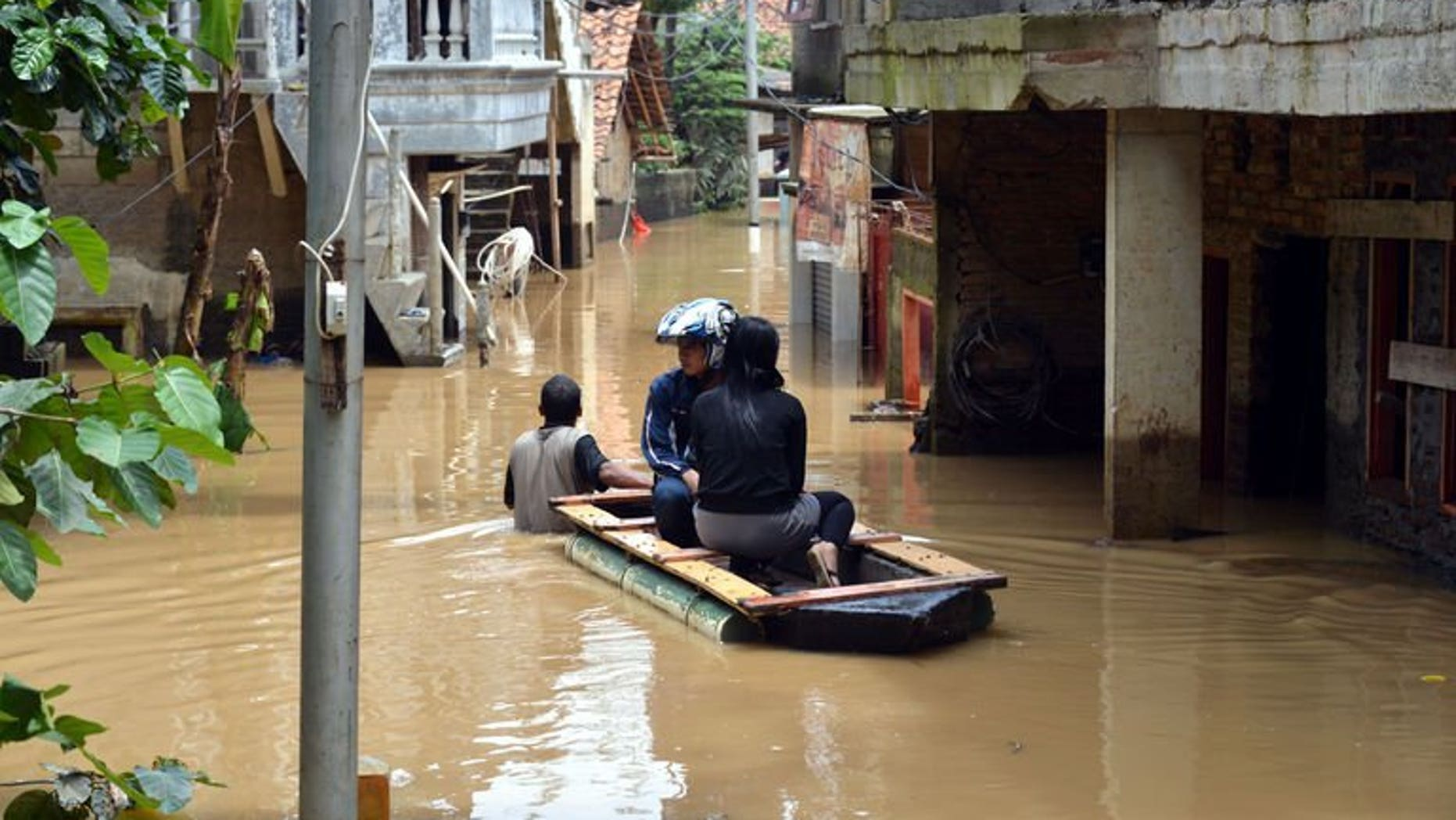 File picture shows residents in an improvised raft travelling down a flooded lane in south Jakarta on March 5, 2013 following heavy rains in nearby mountain areas. At least eight people are dead and five are missing after flooding and landslides hit eastern Indonesia, an official said on Tuesday.