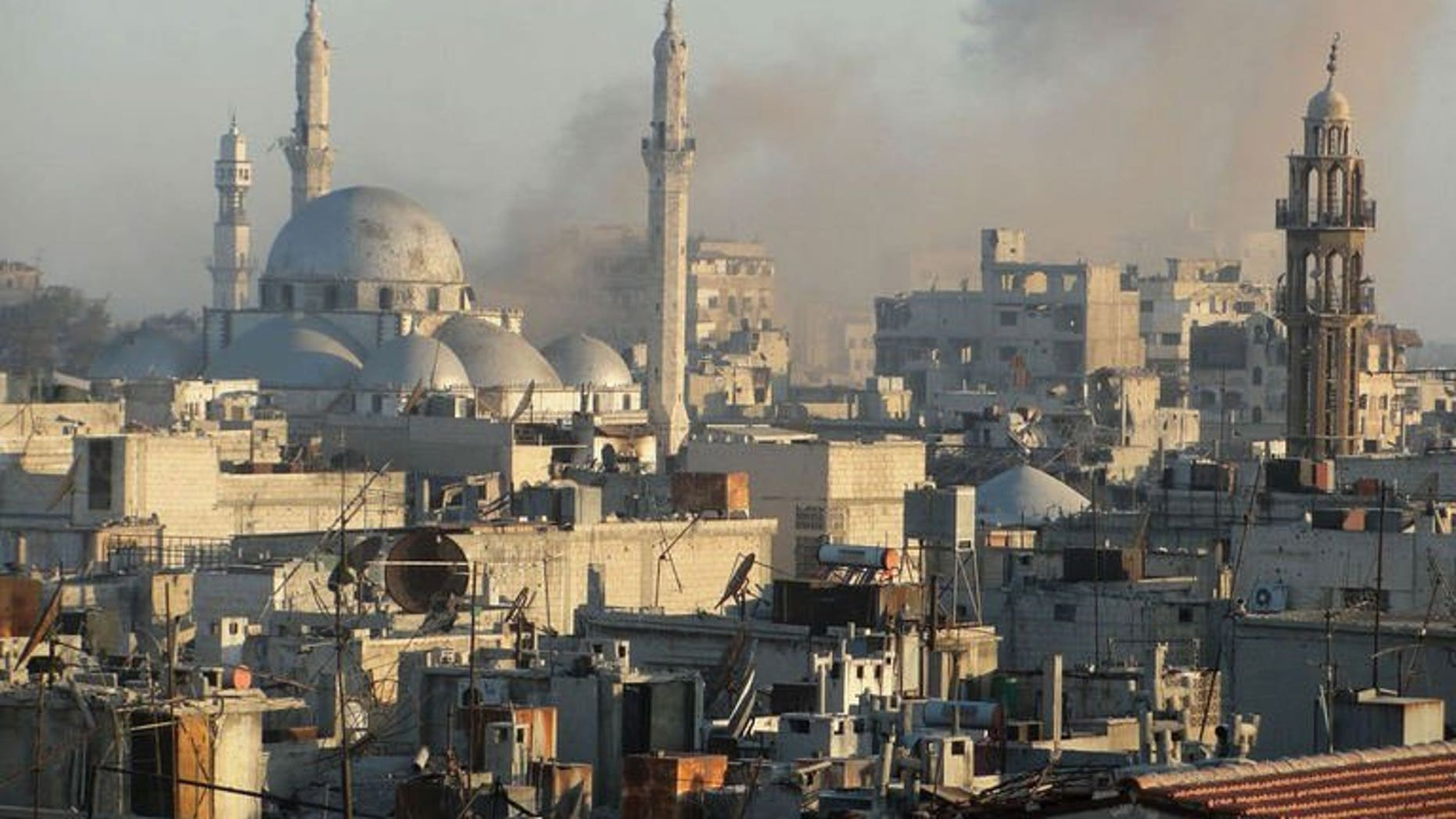 Image released by the Syrian opposition's Shaam News Network on July 27, 2013, claims to show smoke billowing from buildings near Khaled bin Walid mosque in the Khalidiyah neighbourhood of the central Syrian city of Homs. Seven children in the northern Syrian province of Aleppo and another four in Homs were among 17 civilians killed in air raids on Tuesday, a watchdog said.