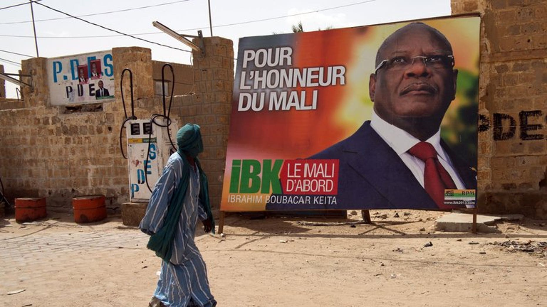 "A man walks past an electoral placard of Ibrahim Boubacar Keita (dubbed IBK) reading ""For Mali's Honor"" on July 24, 2013 in a street of Timbuktu. Mali's former prime minister Keita has taken a wide lead in the presidential poll, initial results showed Tuesday."