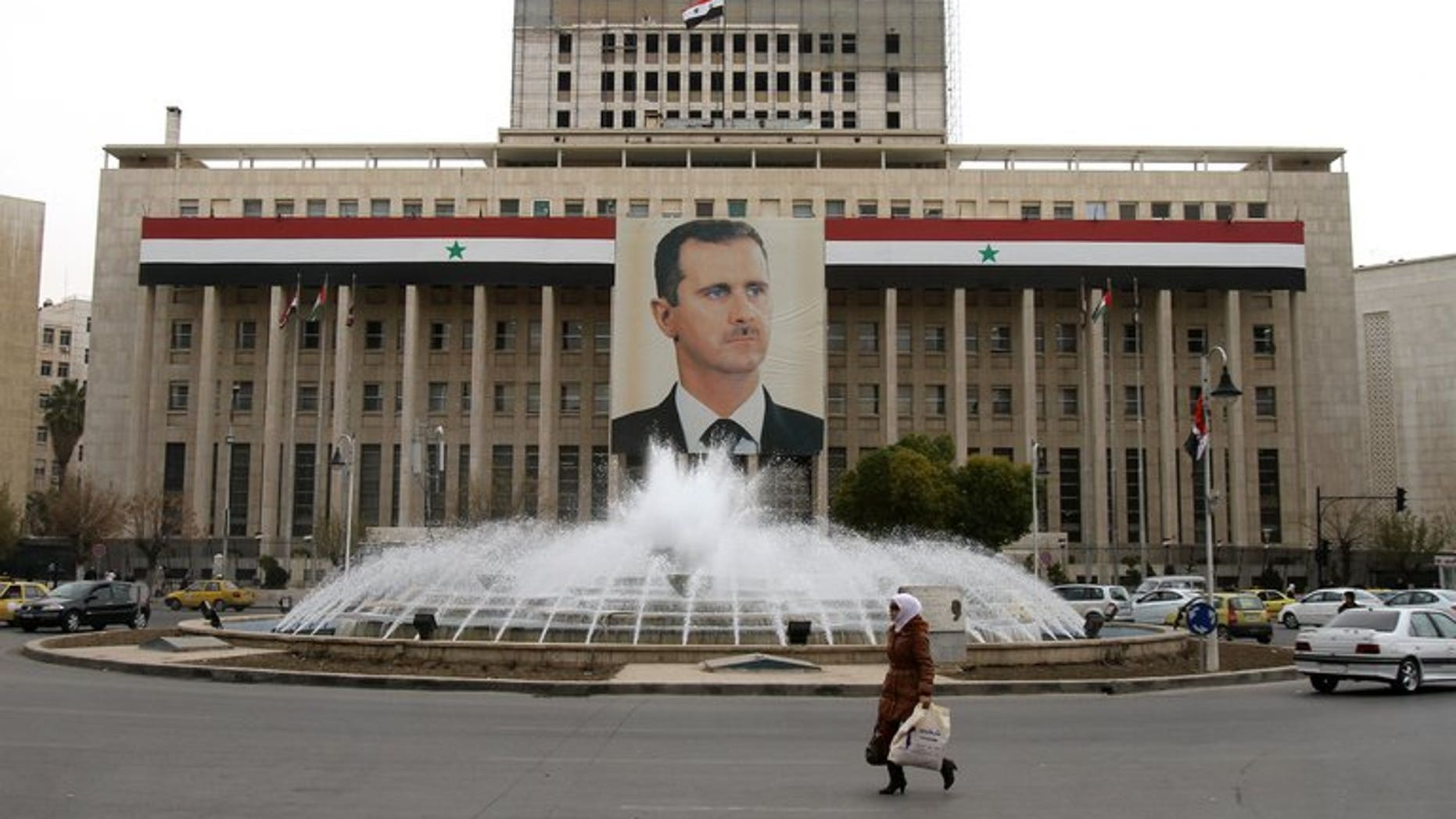 A woman walks past the central bank building decorated with a huge banner of President Bashar al-Assad in the capital in Damascus on February 28, 2012. Iran has agreed to supply Damascus with $3.6 billion in oil in exchange for the right to invest in the country, Syria's state news agency SANA said on Tuesday.