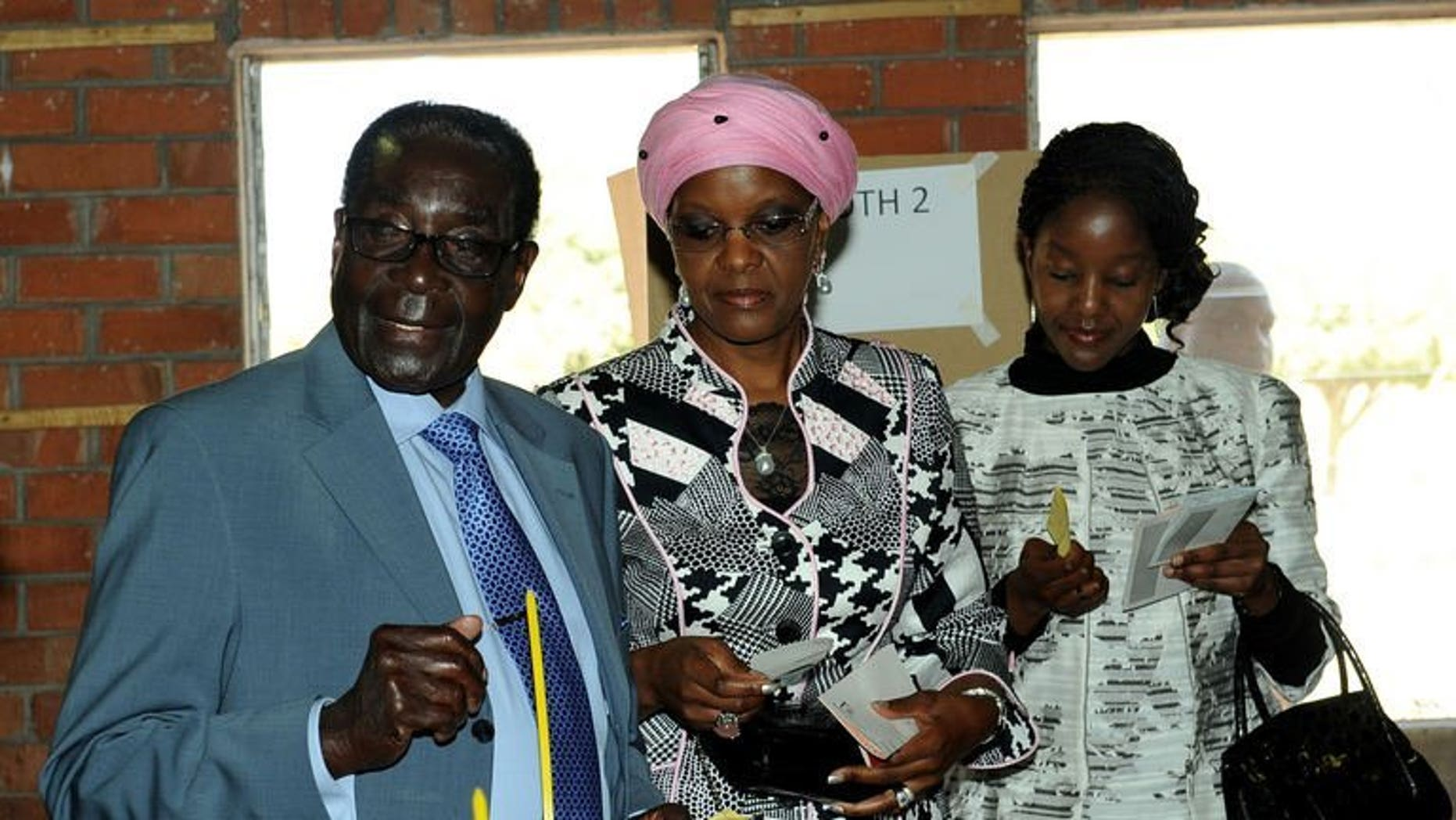 """Zimbabwe President Robert Mugabe (L) casts his vote with his wife Grace and daughter Bona (R) at a polling booth in a school in the capital Harare on July 31, 2013. Mugabe dismissed allegations of vote rigging in elections on Wednesday, saying that is just """"politicking""""."""