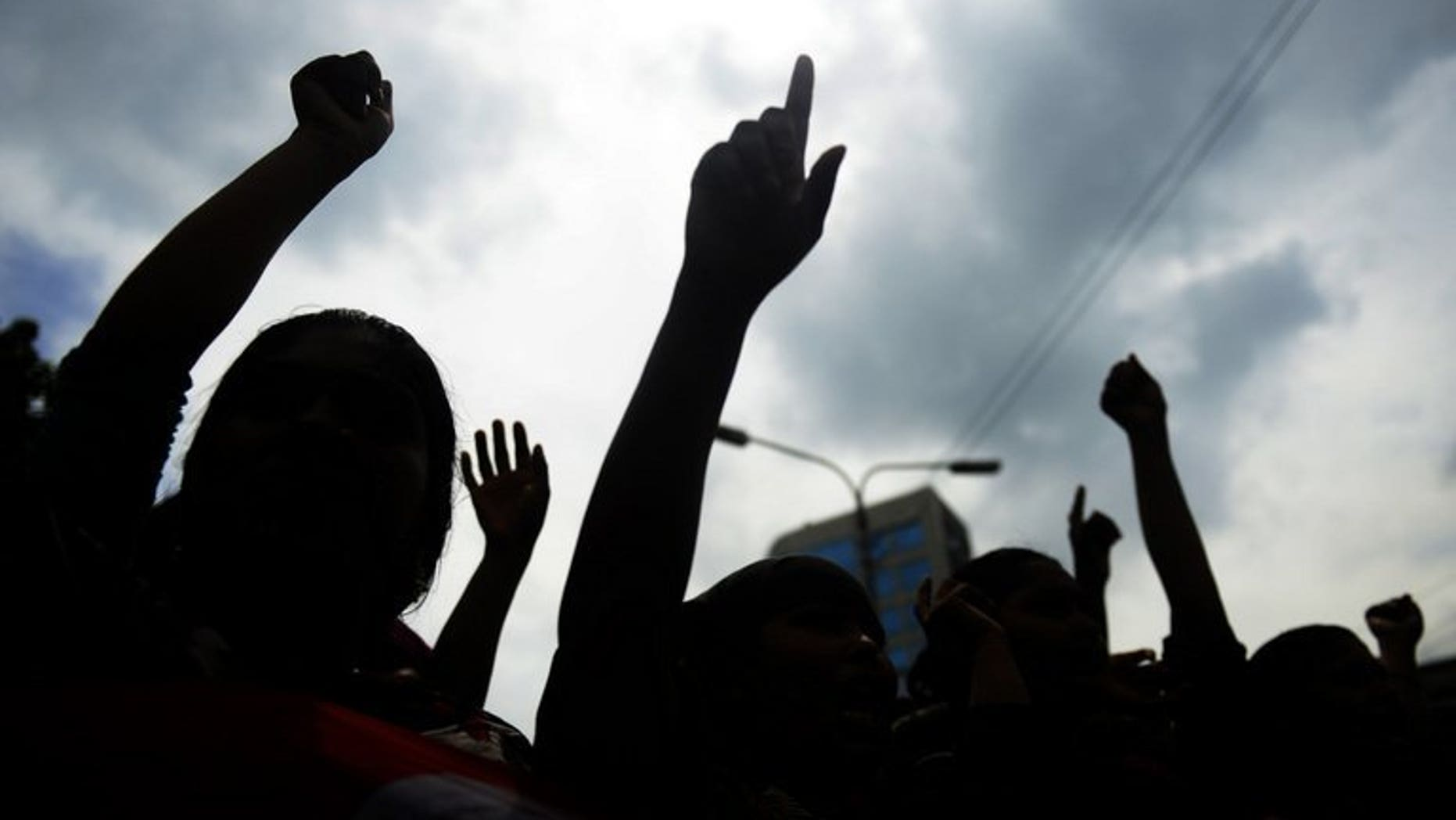 Bangladeshi garment workers shout slogans during a protest in Dhaka, on July 14, 2013. Hundreds of Bangladeshi garment workers have set fire to their factory to demand a better bonus before the country's main Muslim festival. police tell AFP.