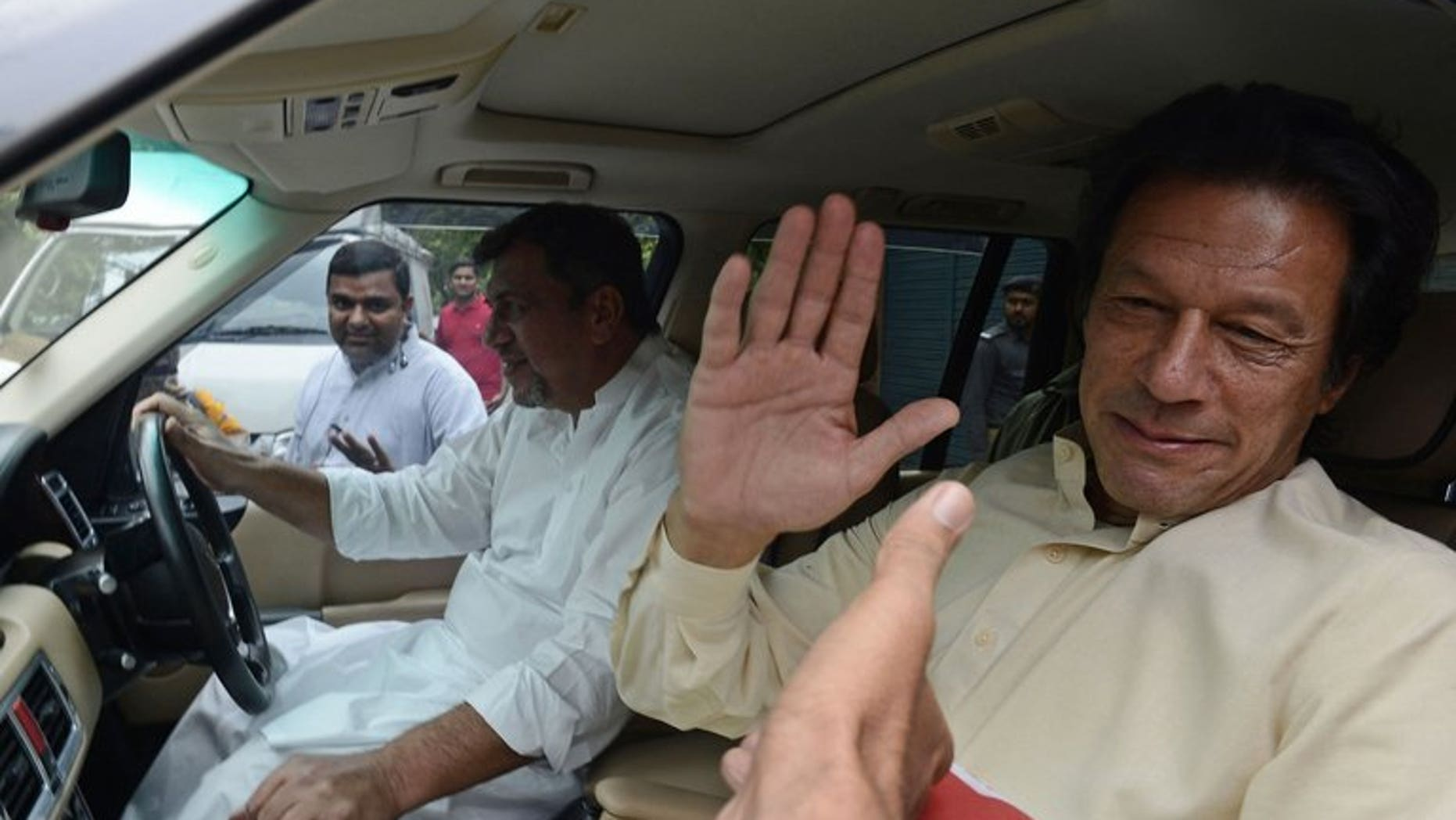 """Pakistan Tehreek-e-Insaf (PTI) chairman Imran Khan greets supporters in Lahore on June 13, 2013. Pakistan's top court on Wednesday summoned cricketer-turned-politician Khan for a contempt hearing over his """"critical and derogatory"""" remarks against the judiciary, a statement said."""