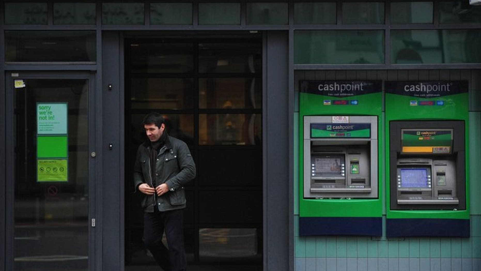 A man leaves a branch of Lloyds TSB bank in central London on March 1. Britain's state-rescued Lloyds Banking Group on Thursday announced a return to first-half net profits as the government looks to return the lender to the private sector.
