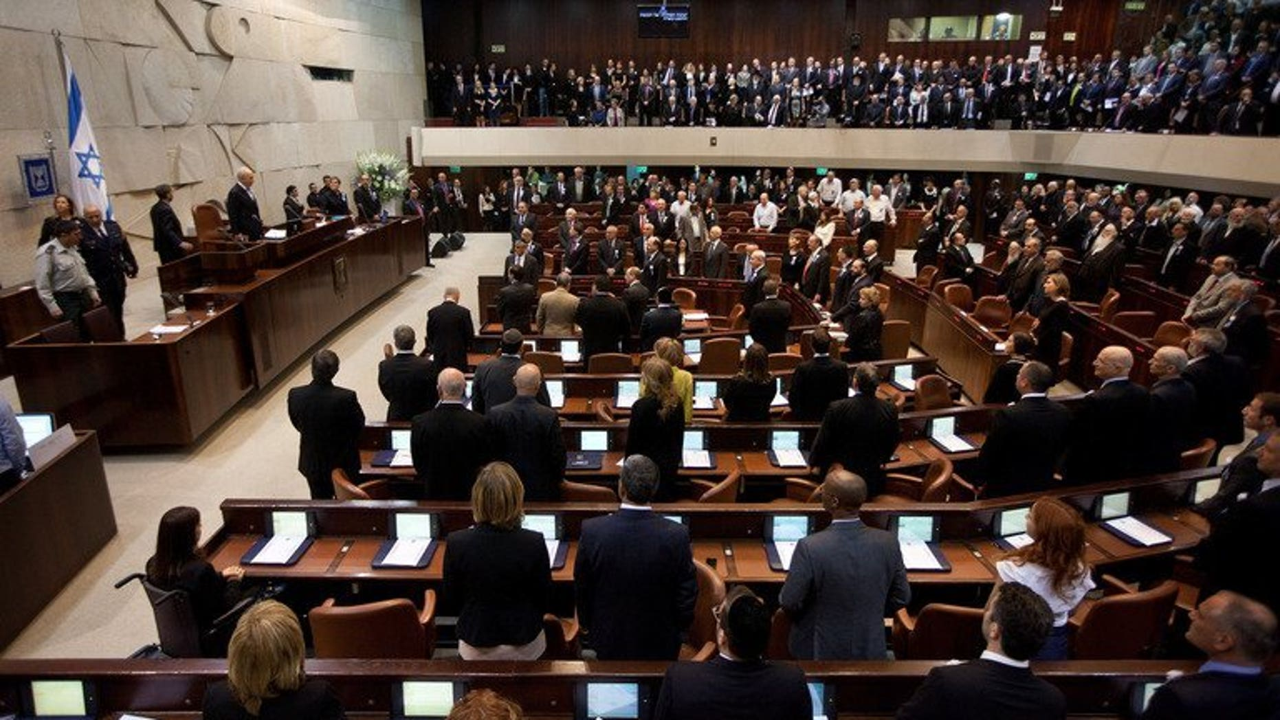 Israeli lawmakers stand during a swearing-in ceremony at the Knesset in Jerusalem, on February 5, 2013. Israel's parliament has taken the first tentative steps towards reining in the country's extreme form of proportional representation in a bid to make governments more stable.