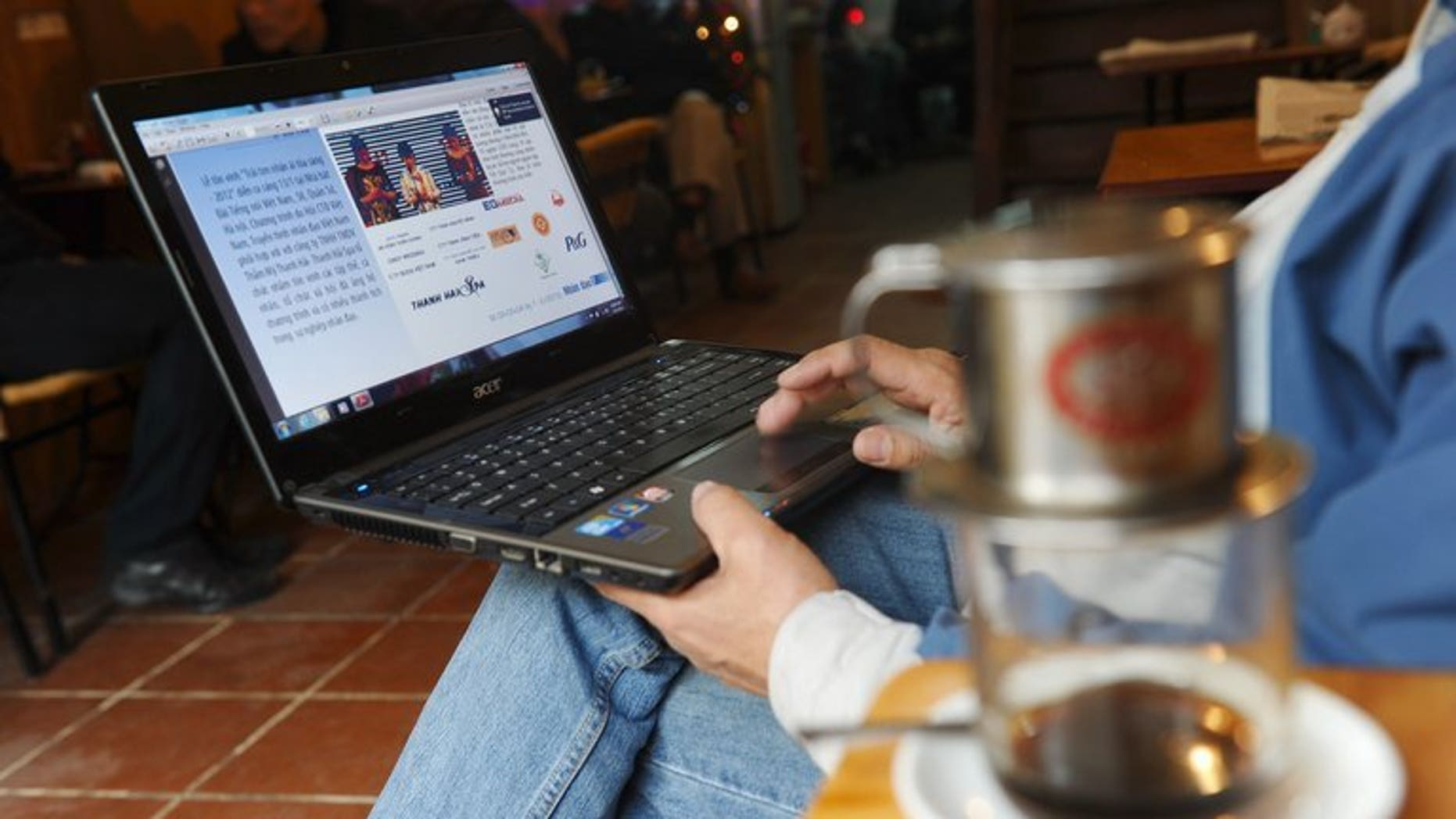 A man reads online news with his laptop at a coffee shop in downtown Hanoi on January 15, 2013. Communist Vietnam is to ban bloggers and social media users from sharing news stories online, under a new decree seen as a further crackdown on online freedom.