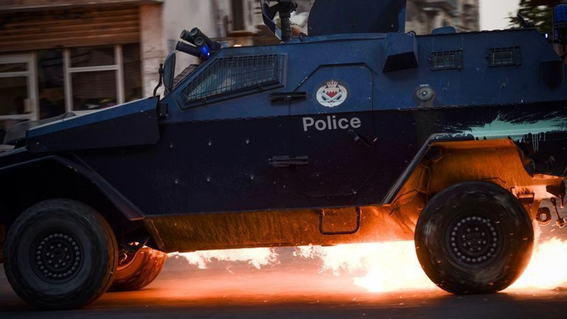 """A Bahraini riot-police car is hit by a petrol bomb during clashes in the village of Saar, on June 26, 2013. Bahrain's King Hamad has decreed stiffer penalties for """"terror acts"""" in the country rocked by a Shiite-led uprising since 2011, according to the official BNA news agency."""