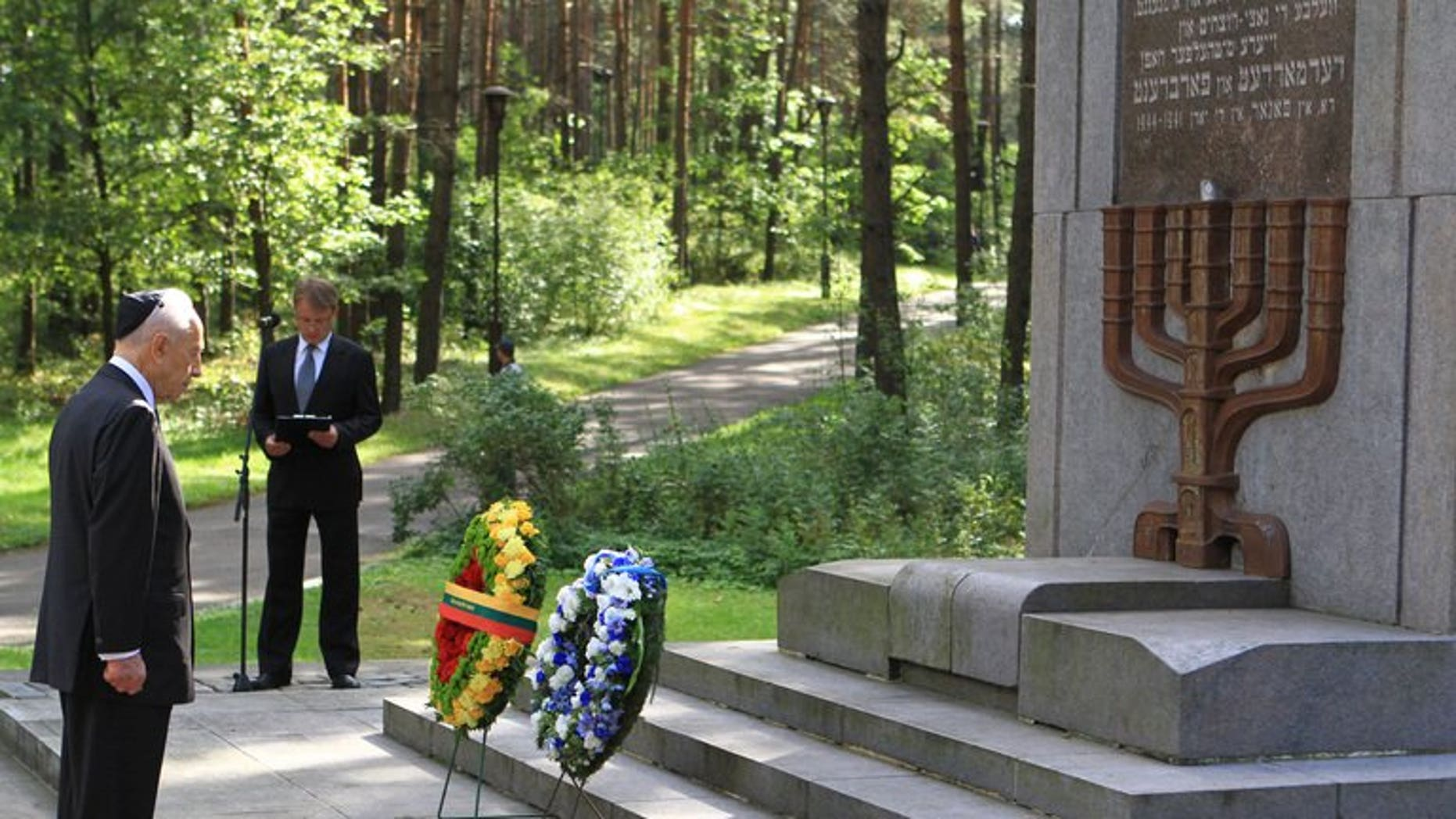 Israeli President Shimon Peres pays his respect after laying a wreath at the Paneriai memorial in Vilnius, on August 1, 2013.