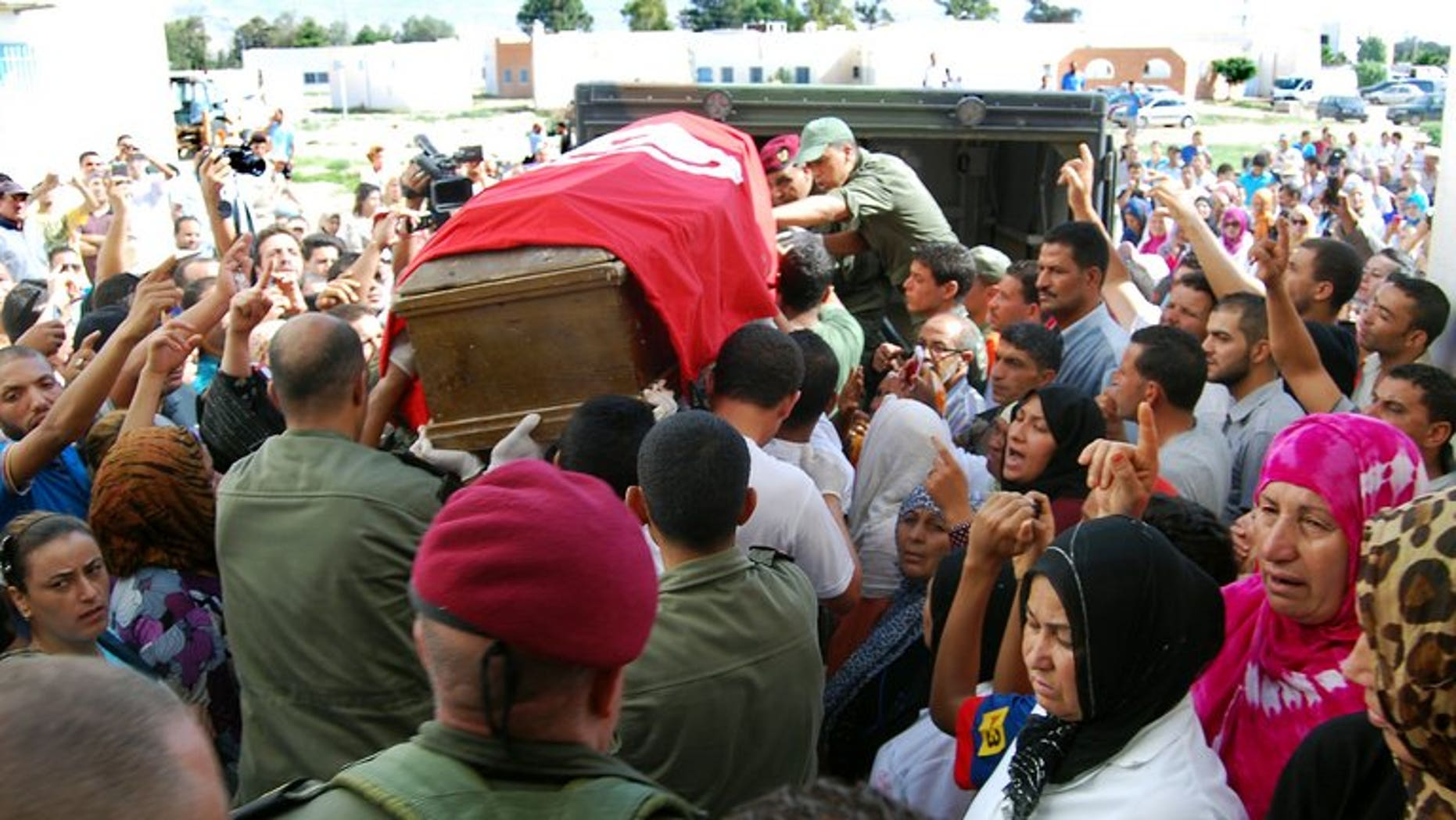 Tunisian soldiers carry the coffin, draped in the Tunisian flag, of one of the eight soldiers that was slain by militants in an ambush near the Algerian border, as they leave the hospital in Kasserine on July 30, 2013. Algeria's army has reinforced its forces along the eastern border with Tunisia, Interior Minister Daho Ould Kablia said on Thursday, days after the killing.