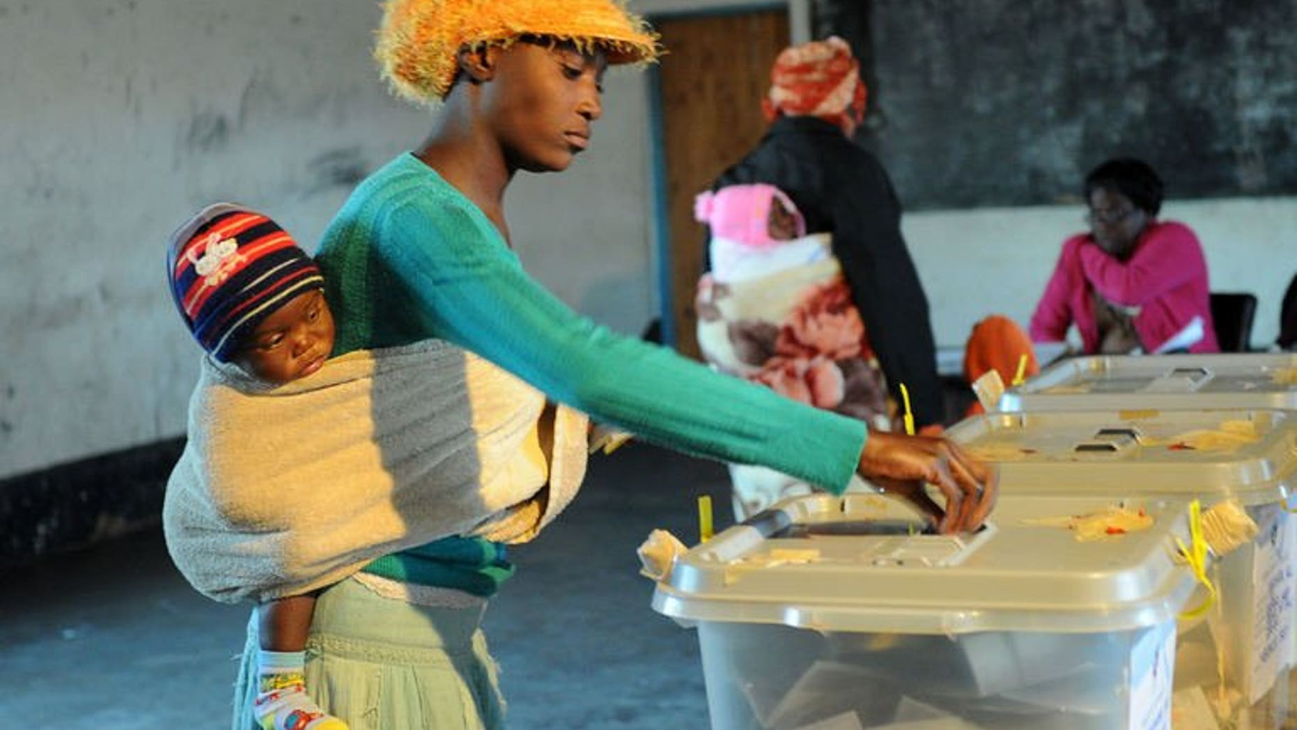 A Zimbabwean mother holding her child casts her ballot at a polling station on July 31, 2013 in Domboshava, 60km north of Harare. The first official results from Zimbabwe's disputed national assembly elections showed President Robert Mugabe's party gaining an early and overwhelming lead Thursday.