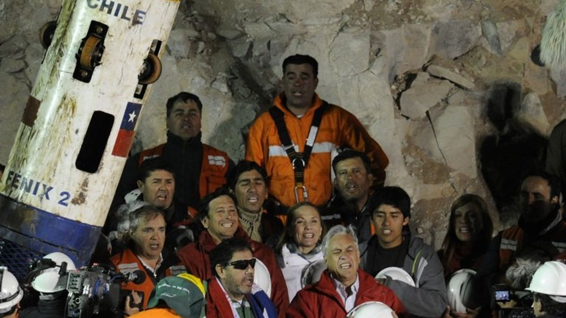 The last of the 33 Chilean miners to be rescued, Luis Urzua (C-L), signs the national anthem alongside Chilean President Sebastian Pinera (C-R) and rescue workers, near Copiapo, Chile on October 13, 2010. Three years after 33 trapped Chilean miners were rescued in an operation that captivated the world, an investigation into the site's management closed without any charges.