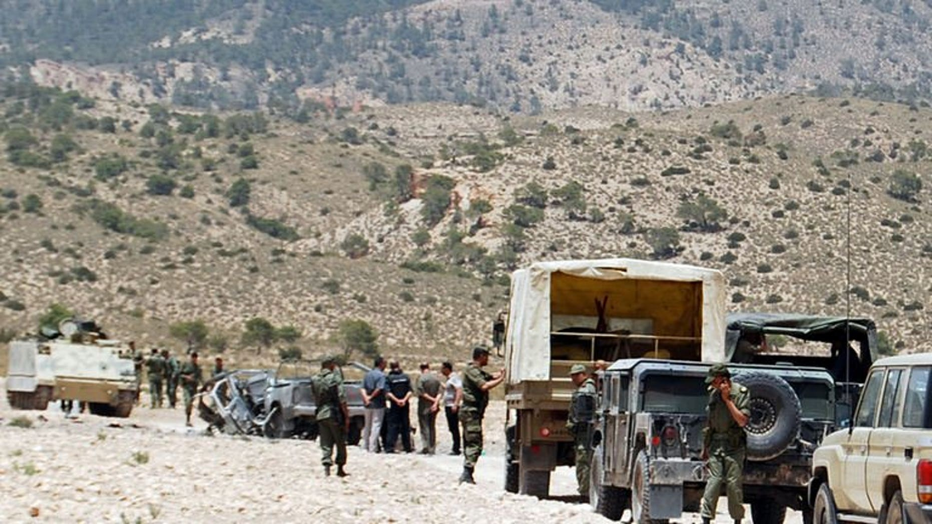 """Tunisian army stand guard near a demolished vehicle following a roadside bomb in the mountainous border region near Algeria on June 6, 2013. The Tunisian army launched an offensive early Friday against a group of """"terrorists"""" near the Algerian border, where eight Tunisian soldiers were killed earlier this week, a military source told AFP."""
