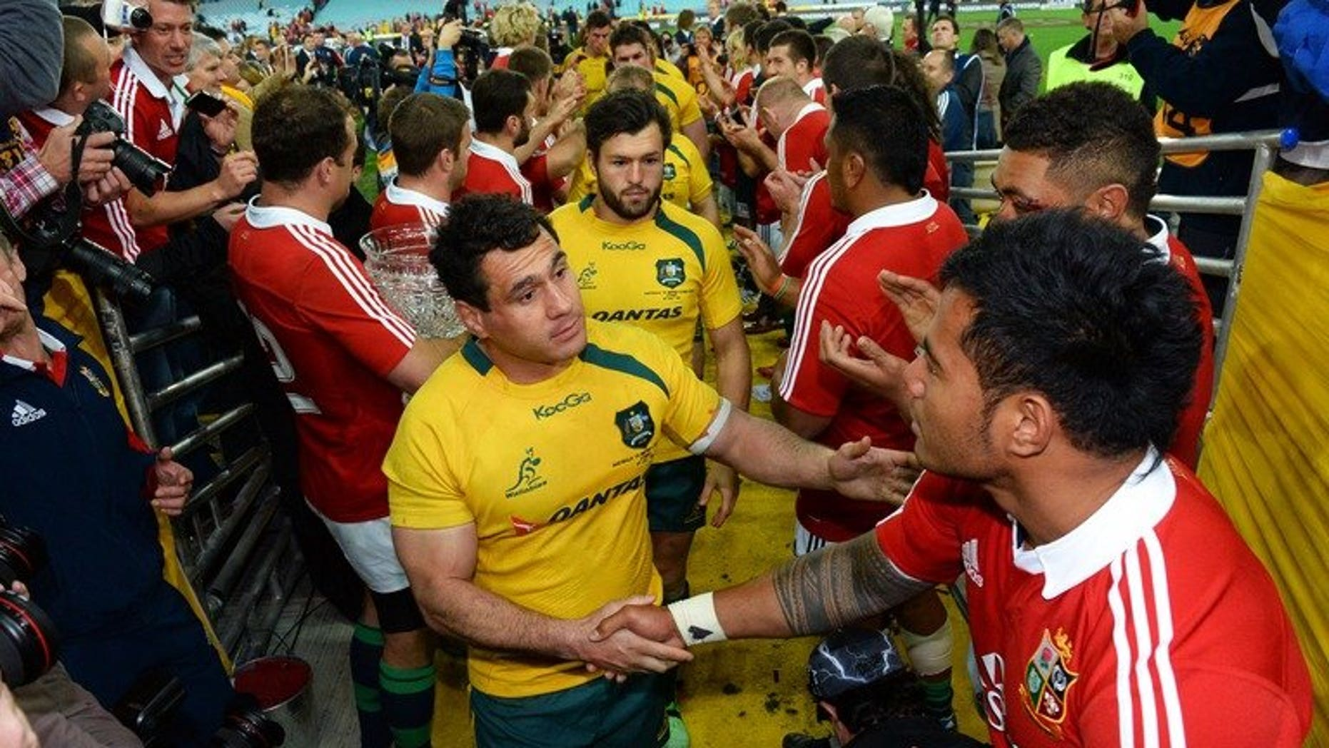 Australian Wallabies flanker George Smith (C) shakes hands with British and Irish Lions centre Manu Tuilagi after the Lions defeated the Wallabies in their third Test, match played in Sydney on July 6, 2013. The Wallabies may have lost the series but Australia did very well financially out of the recent rugby tour by the Lions, a tourism industry body said on Friday.