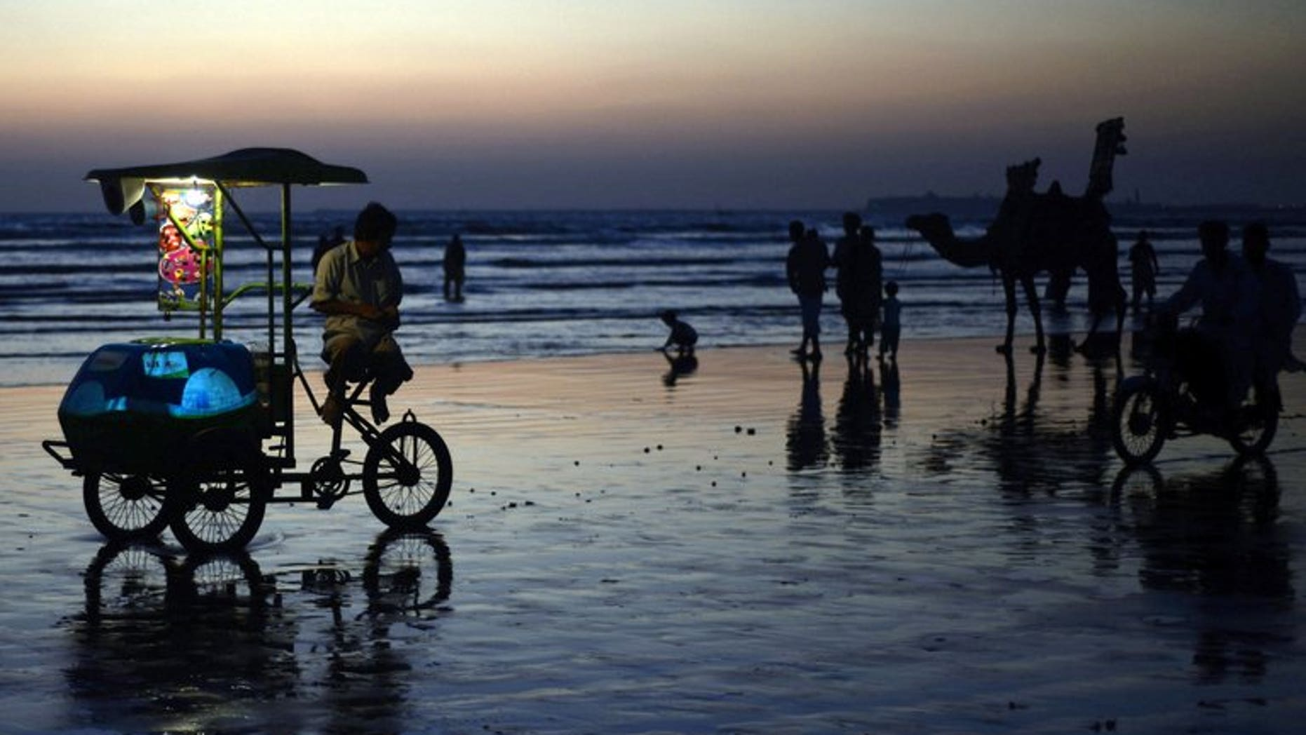 In this file photo, people are seen gathering on Sea View Beach during sunset in Karachi, on November 5, 2012. A charismatic Muslim preacher criticised for giving out babies to childless couples live on prime-time Pakistani television denies he is crudely seeking top ratings and insists he is spreading charity.