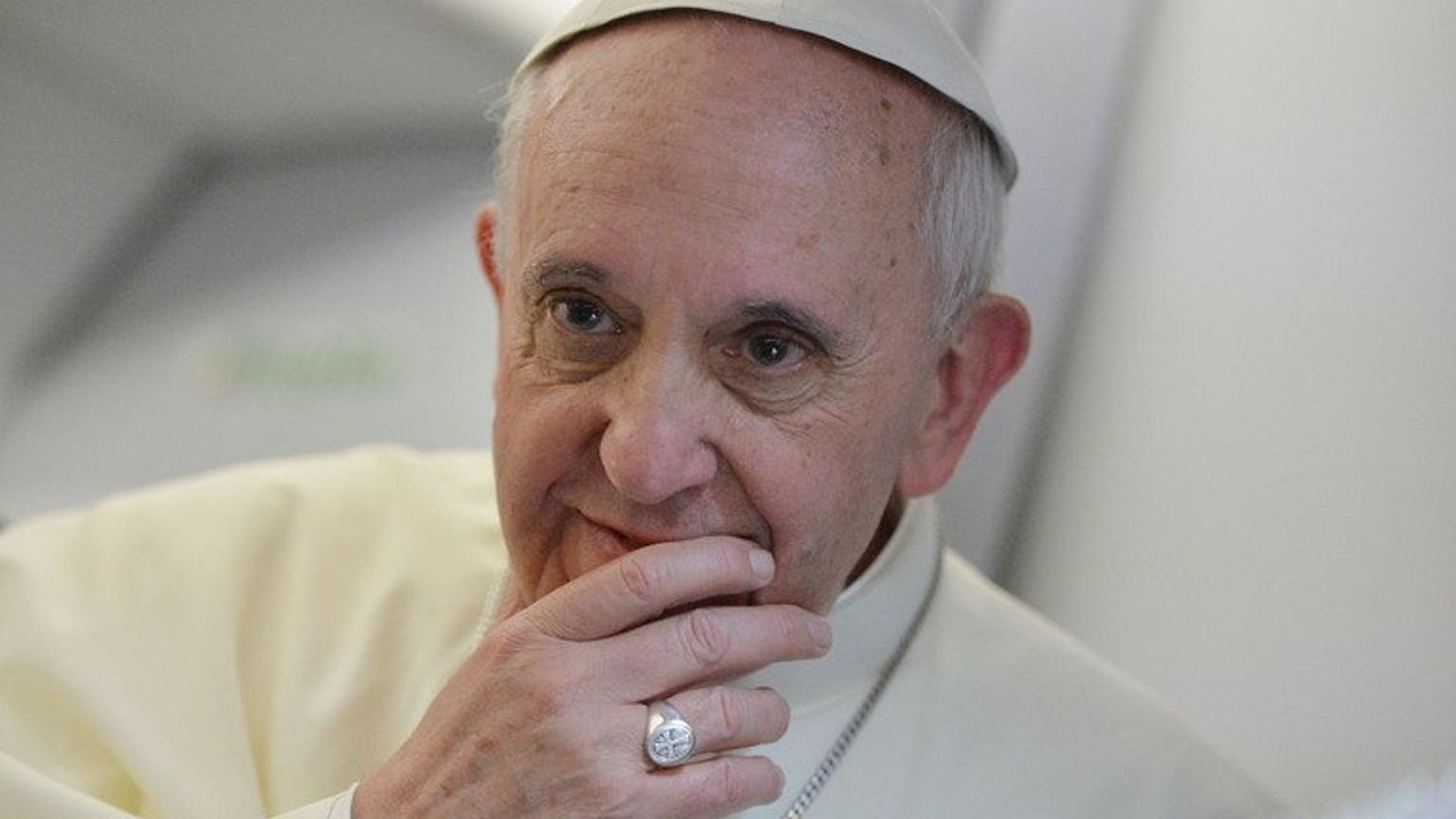 """Pope Francis listens to a question during a press conference held aboard the papal flight on July 28, 2013. The pontiff has called for """"mutual respect"""" between Christianity and Islam and an end to """"unfair criticism"""" in a personal message congratulating Muslims on the feast of Eid al-Fitr."""