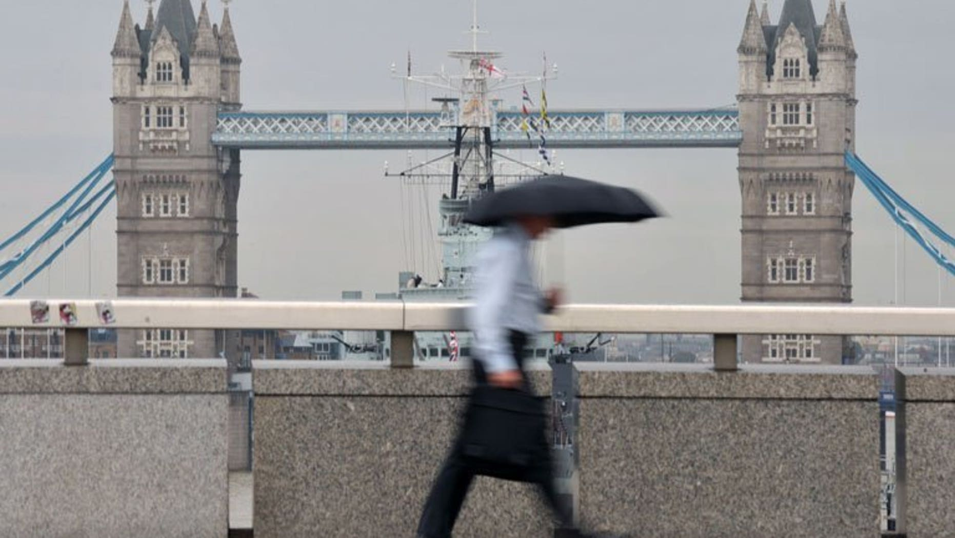 A city worker walks over London Bridge in central London. London shares closed lower on Friday as markets tumbled on weak US nonfarm payroll employment figures, with sharp drops in William Hill and Smiths Industries accentuating the fall, dealers said.