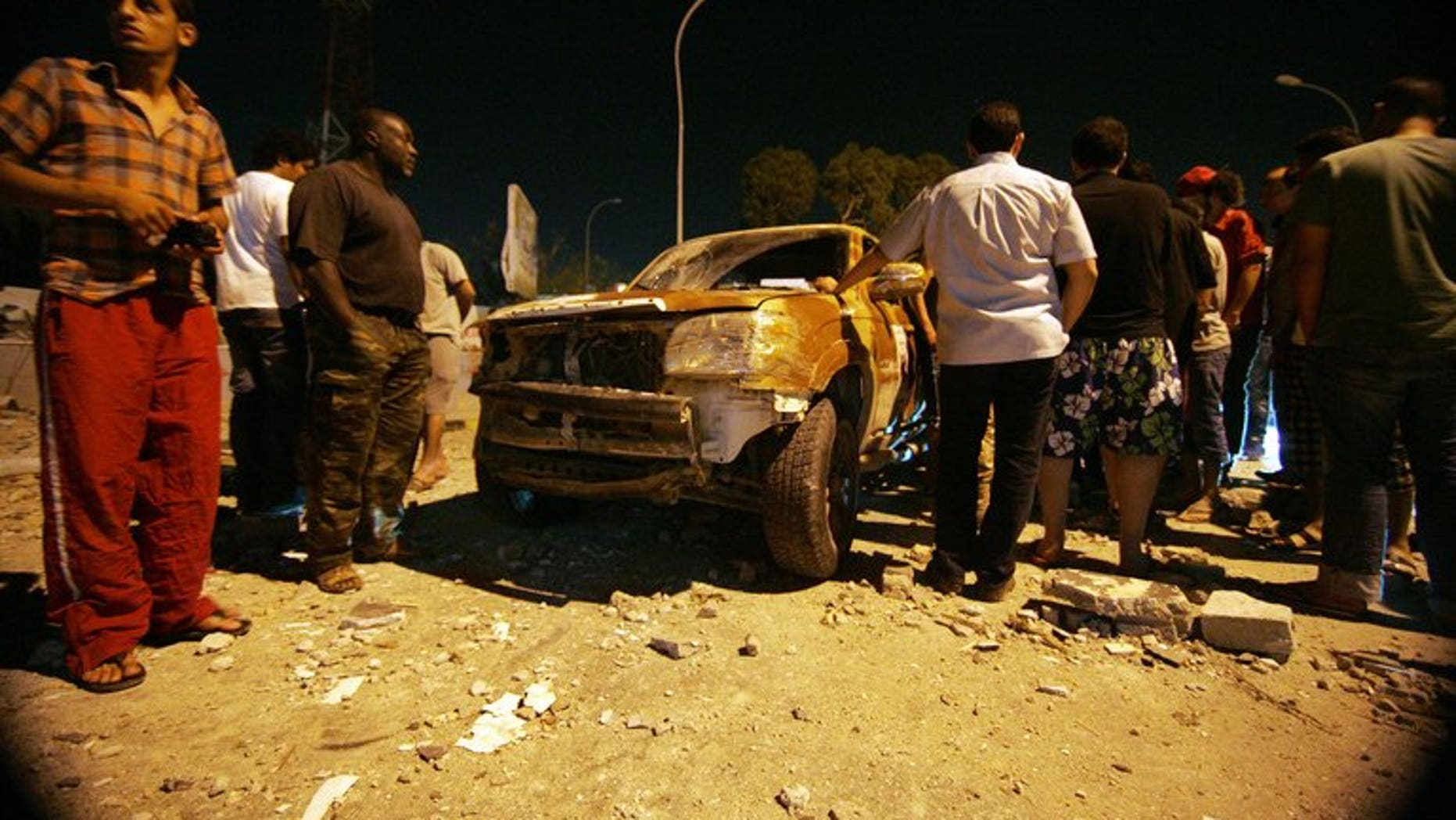 Benghazi residents and security forces gather around a damaged car at the site of an explosion at the al-Hadeiq police station on June 19, 2013.