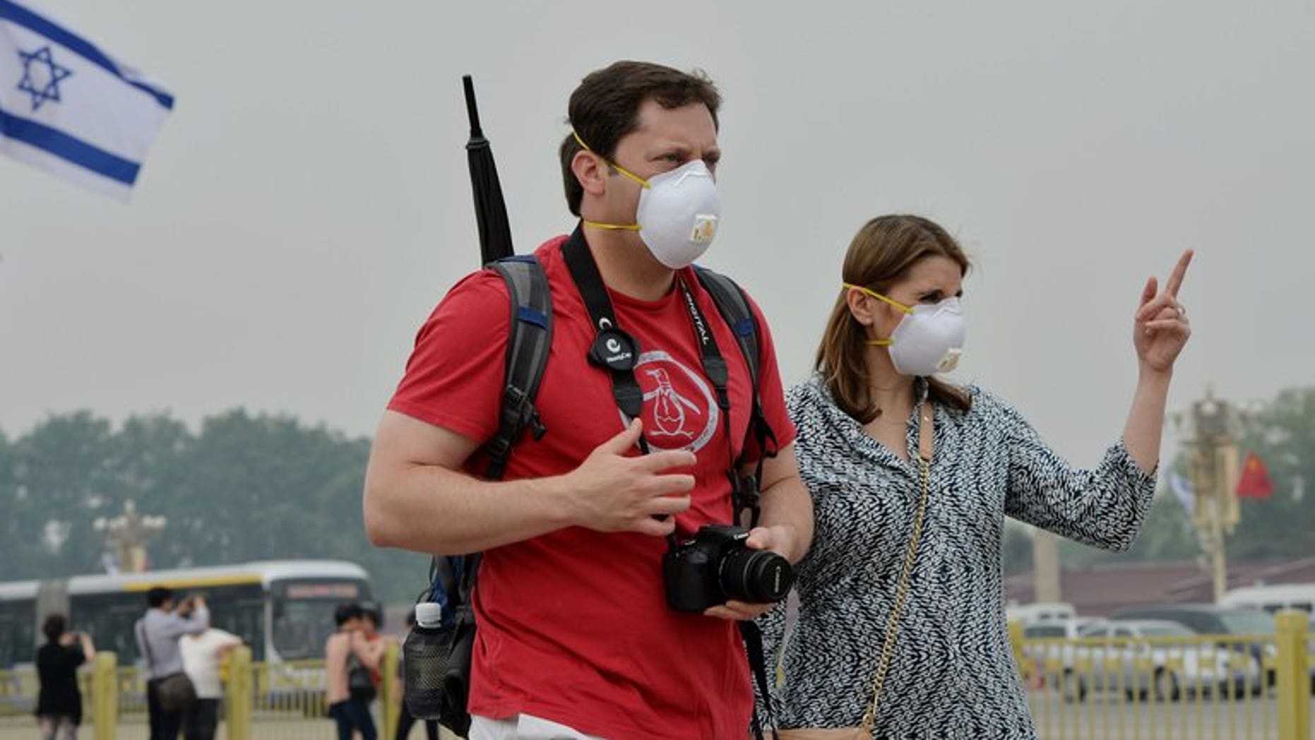 Two tourists wear face masks as they visit Tiananmen Square on a heavily polluted day in Beijing on May 8, 2013. The number of tourists visiting Beijing fell by more than 14% in the first half of this year compared to 2012, with air pollution blamed for the decline.