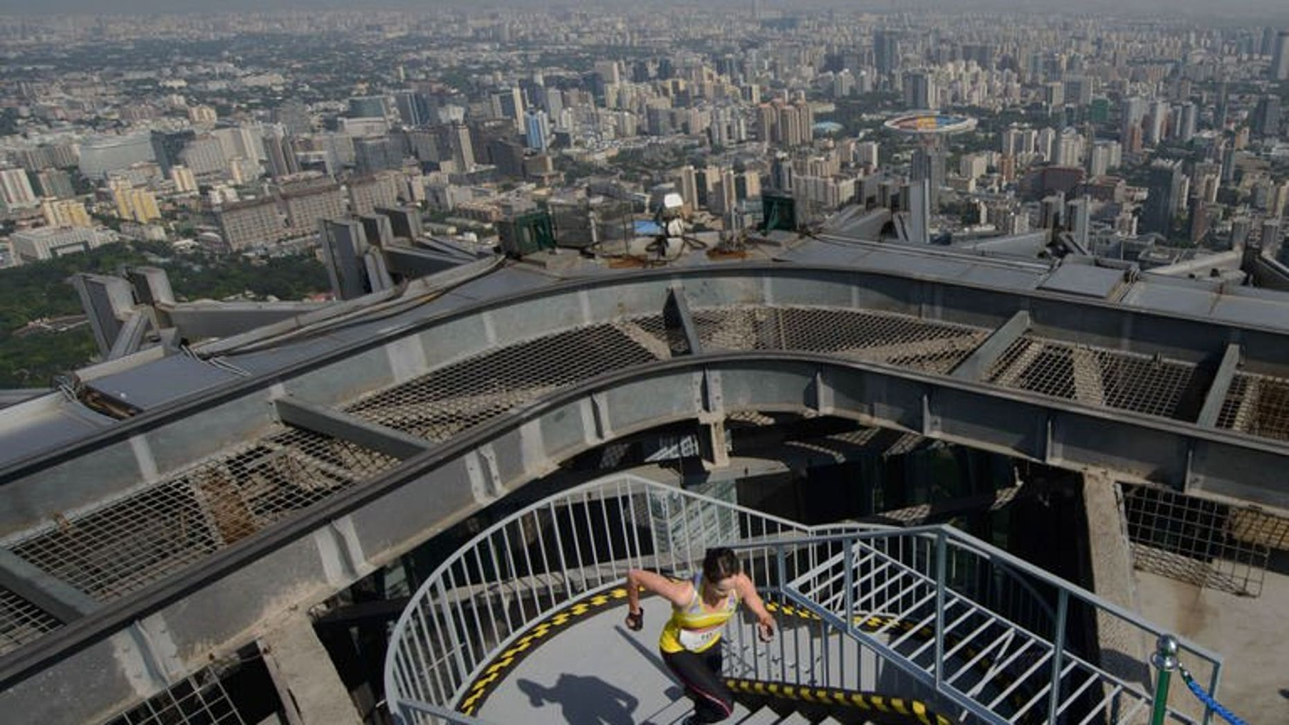"""A runner arrives at the top of the China World Trade Center Tower 3 during a """"vertical run"""" on August 3, 2013. Around 600 runners sprinted their way up 82 floors as the country's first ever """"vertical run"""" was held in a Beijing skyscraper on Saturday."""