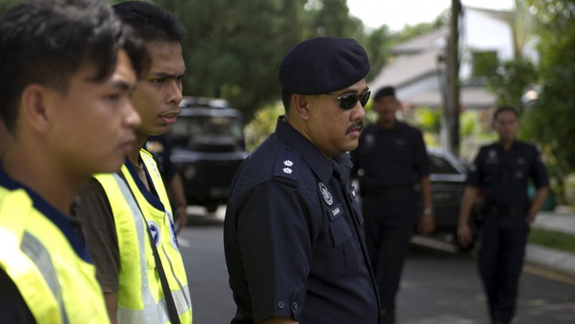 Malaysian police officers pictured during a road block in downtown Kuala Lumpur on March 16, 2012. Six family members who suffocated a Malaysian toddler to death by piling on top of her for hours in a suspected exorcism ritual have been fined but avoided jail, a report said Saturday.