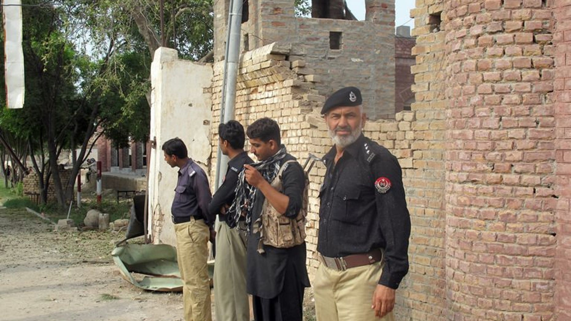 Pakistani policemen stand outside the Central Prison after an overnight armed Taliban militant attack in Dera Ismail Khan on July 30, 2013. The global police agency Interpol has said it suspected Al-Qaeda was involved in recent jailbreaks across nine countries, including Iraq, Libya and Pakistan.