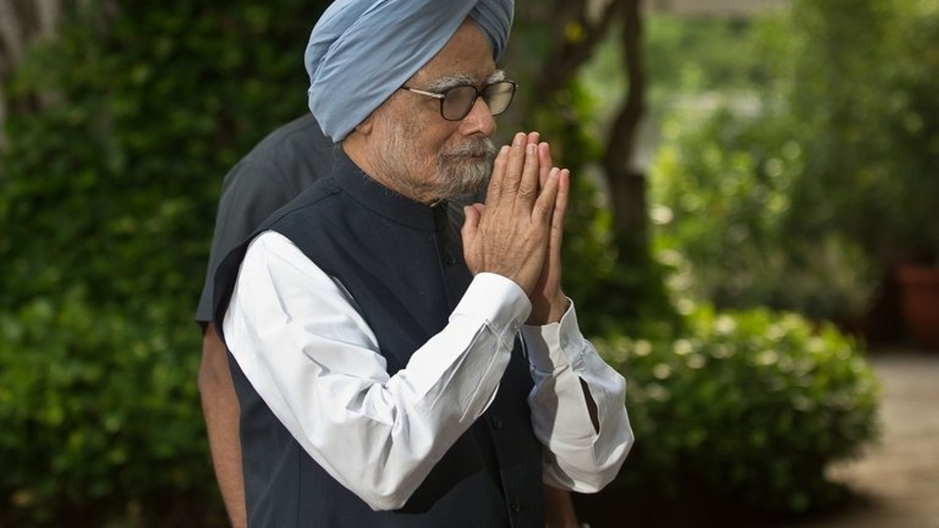 """Indian Prime Minister Manmohan Singh gestures as he arrives for a meeting in New Delhi, on July 30, 2013. Singh has appealed to the opposition to make the next session of parliament """"productive"""" after the last one was cut short by heated rows over allegations of government corruption."""