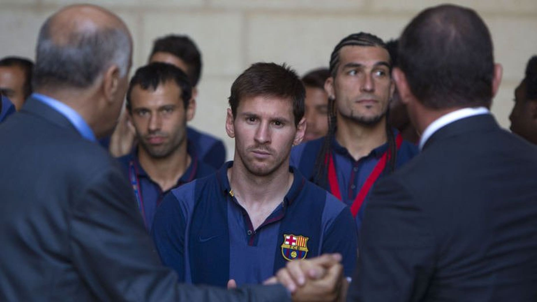 President of FC Barcelona Sandro Rosell (R) and president of the Palestinian Olympic Committee Jibril Rajub (L) shake hands in front of Argentinian forward Lionel Messi (C) at a joint news conference in the West Bank Biblical town of Bethlehem on August 3, 2013.