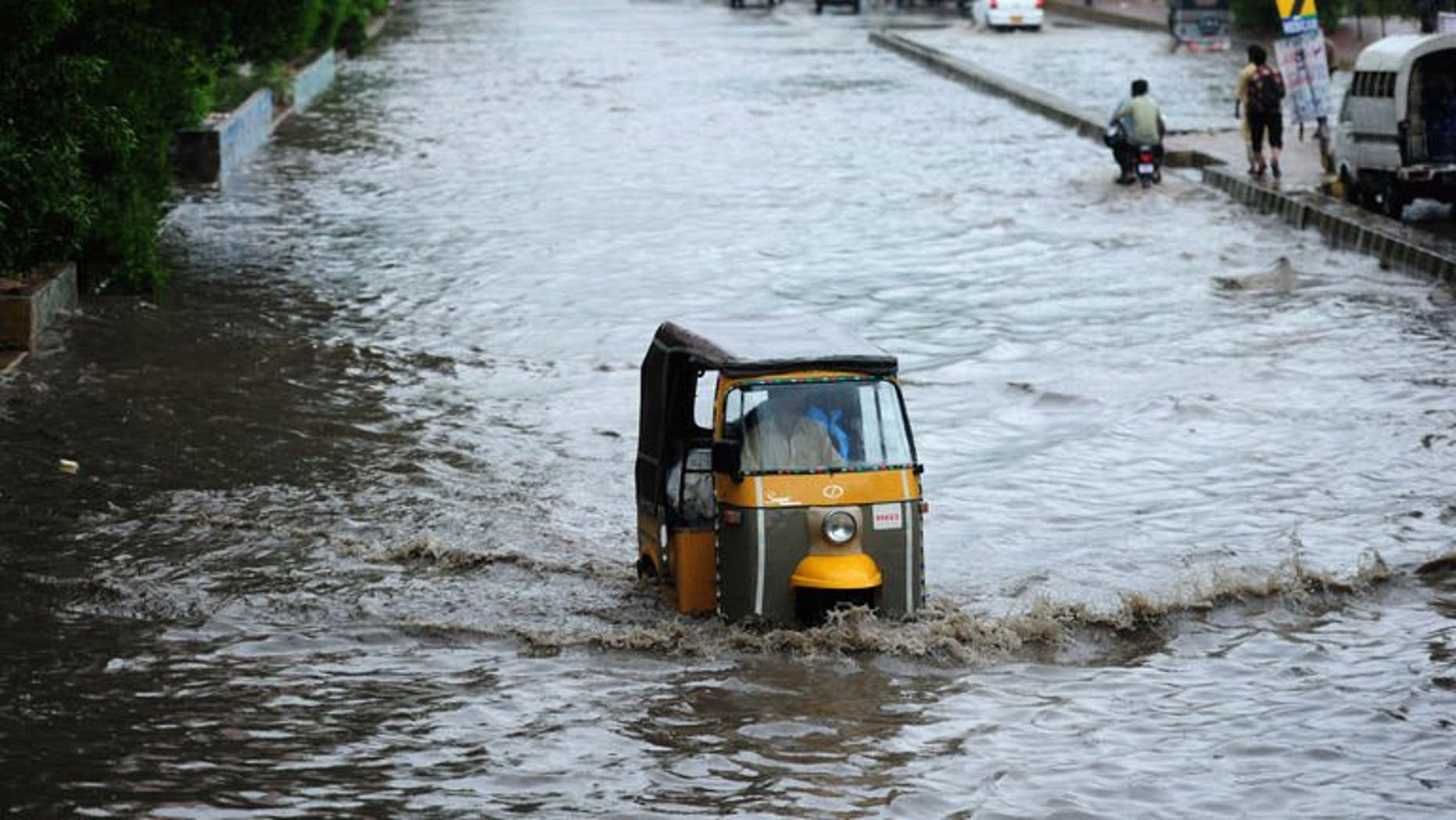 A Pakistani man drives his auto rickshaw along a flooded street after the rains in Karachi on August 3, 2013. At least 17 people were killed across Pakistan on Saturday after heavy monsoon rains caused flooding and roofs to collapse, officials said.