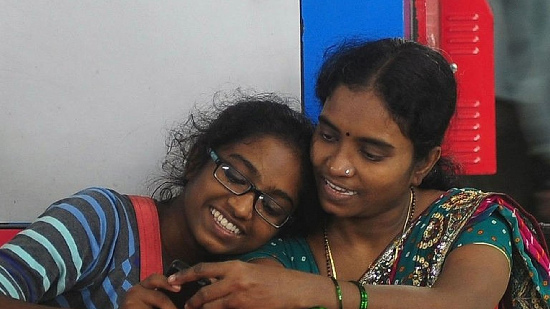 Shweta Katti (L) and her mother Vandana, pictured at a suburbun railway station in Mumbai, on July 30, 2013. Katti, 18, grew up in Mumbai's red-light district facing poverty and sexual abuse but, has overcome the odds to win a scholarship to study in New York, at the liberal arts Bard College, where she hopes to read psychology.