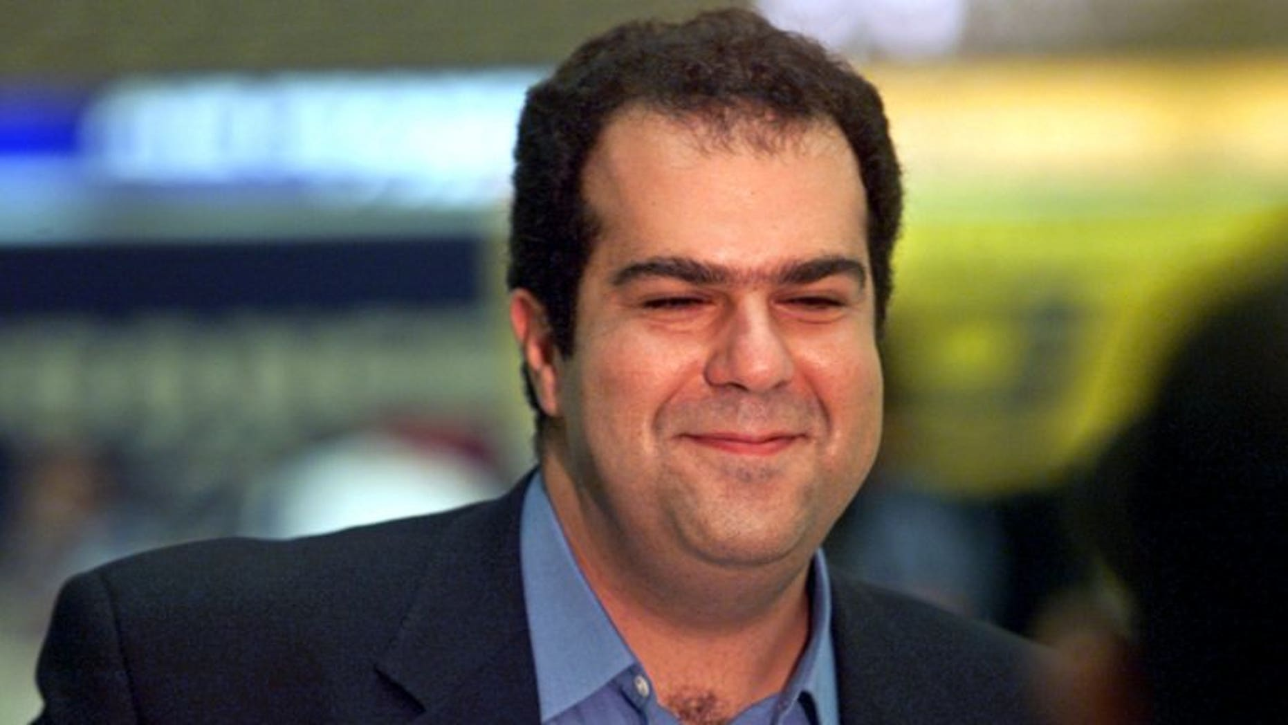 EasyJet tycoon Stelios Haji-Ioannou smiles while waiting to board a flight from Athens to London on September 19, 2000. The easyGroup announced its entry into the food retailing business after the company unveiled plans for a pilot store in London.