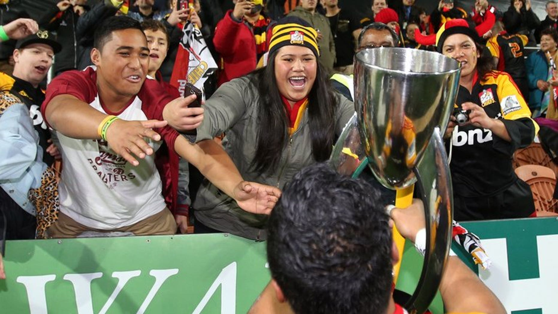Bundee Aki of the Chiefs celebrates with the Super 15 trophy after defeating the ACT Brumbies on August 3, 2013.??Waikato Chiefs became Super Rugby champions with an attacking style.