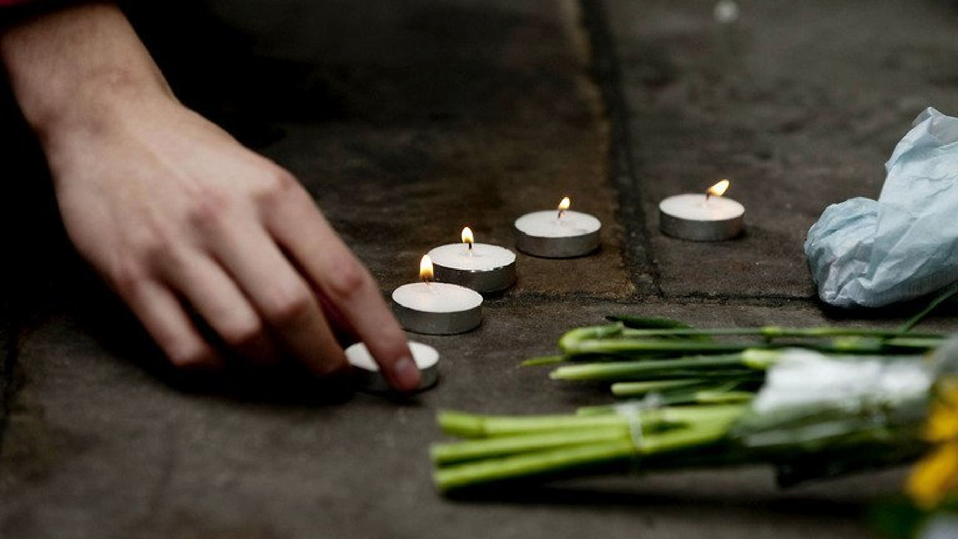 A protester lights a candle at the spot where British newspaper seller Ian Tomlinson died during the G20 demonstrations in London, on April 11, 2009. Metropolitan Police have apologised to Tomlinson's family, who died after being pushed to the ground, and reached an out-of-court setltlement with his family.
