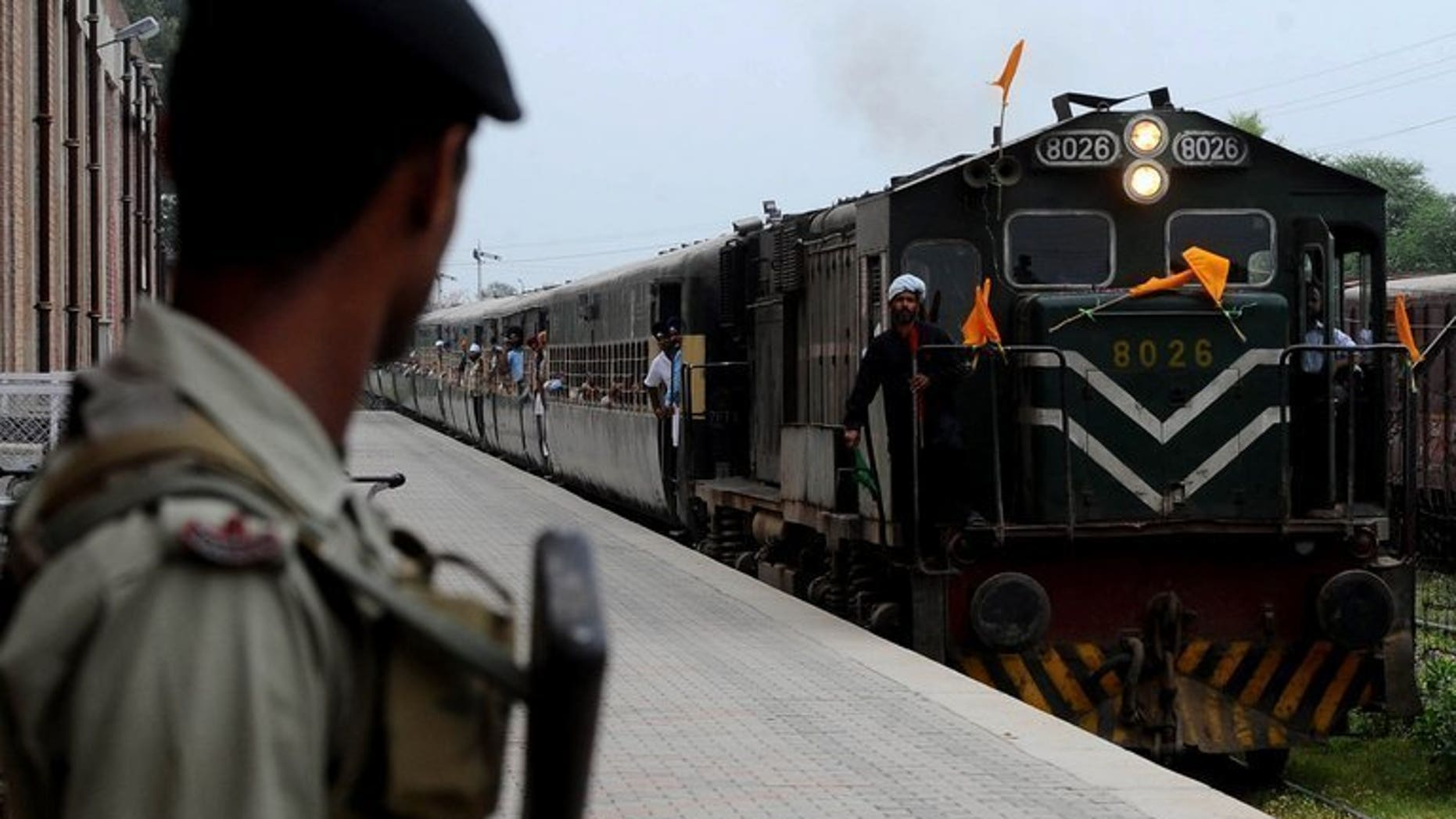 "A Pakistani paramilitary soldier watches a train arriving at Wagah railway station in Wagah, northeast Pakistan on April 10, 2012. A bomb exploded on a passenger train in central Pakistan Monday, killing a toddler and wounding 13 others, officials said, in what the railways minister called ""an act of terrorism""."