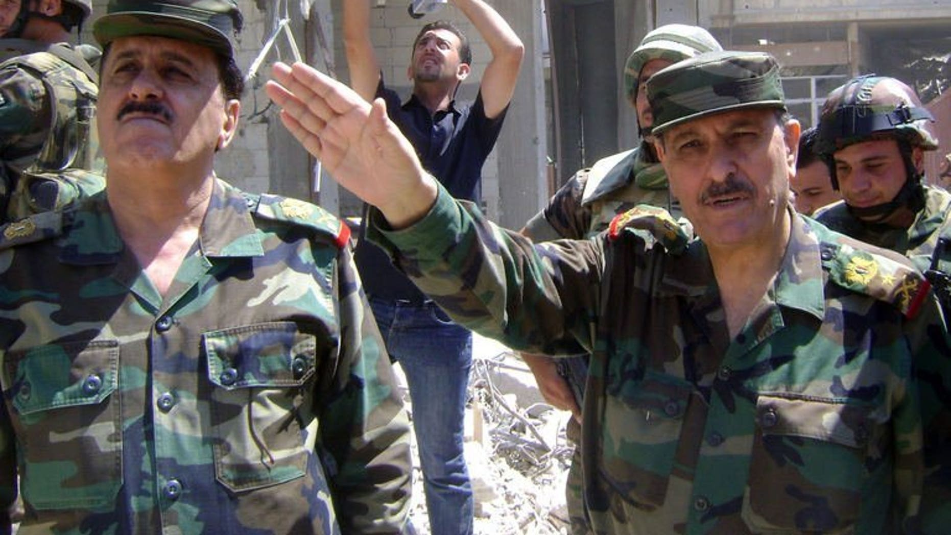 Picture released by the Syrian Arab News Agency (SANA) on August 5, 2013 shows Syrian general Fahd al-Freij (R), Defence minister and chief of the armed forces, talking to the media in the district of Khalidiyah in the central Syrian city of Homs. Freij visited army troops in Khaldiyeh, a district the army won back from rebel control in late July, state news agency SANA said on Monday.