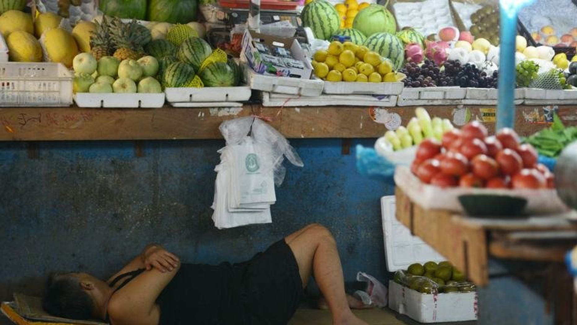 A vendor takes a rest in a market in Shanghai on July 15, 2013. A Chinese vendor's plan to fake his own death at the hands of social enforcers failed when he could not play dead long enough in scorching heat, state media reported Monday.
