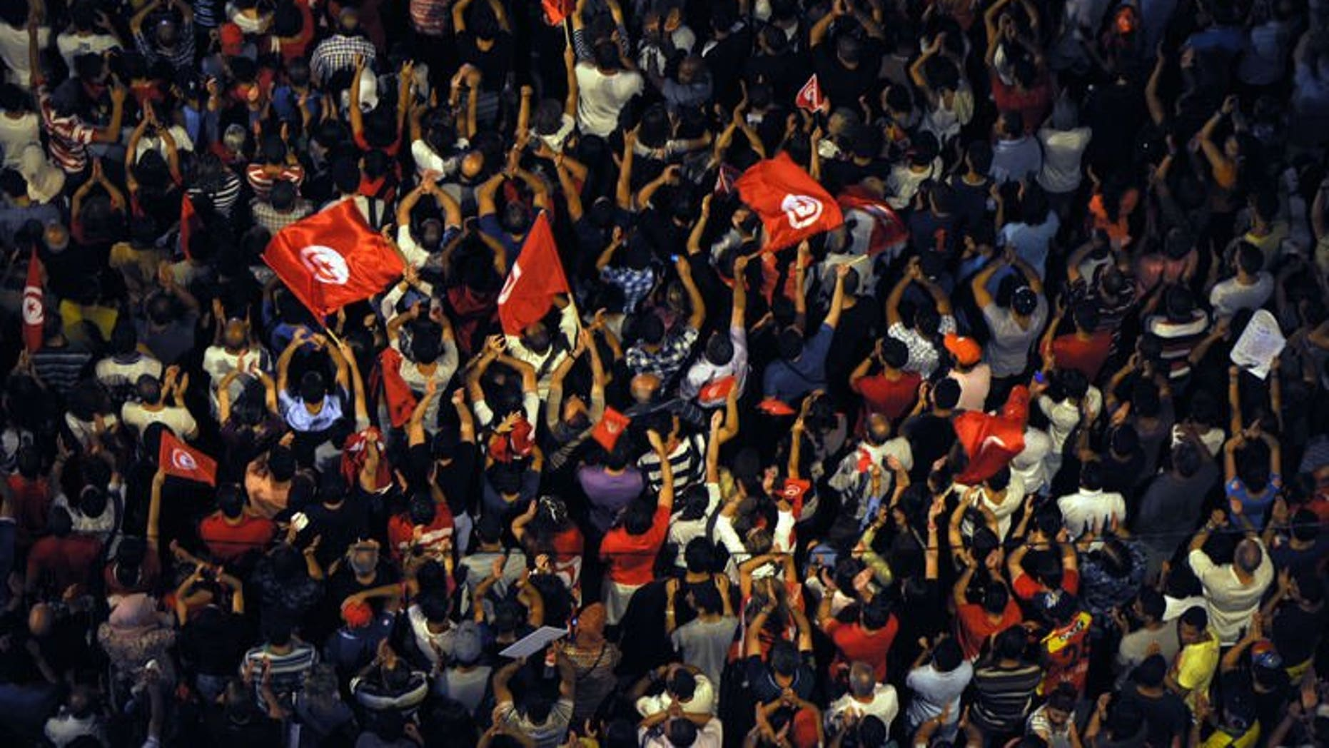 Tunisians wave flags and chant slogans in front of the Constituent Assembly headquarters against the Islamist government on August 4, 2013 in Tunis. Police used batons and tear gas against protesters who tried to break into local government offices in Sidi Bouzid, cradle of the 2011 revolution, an AFP journalist said.