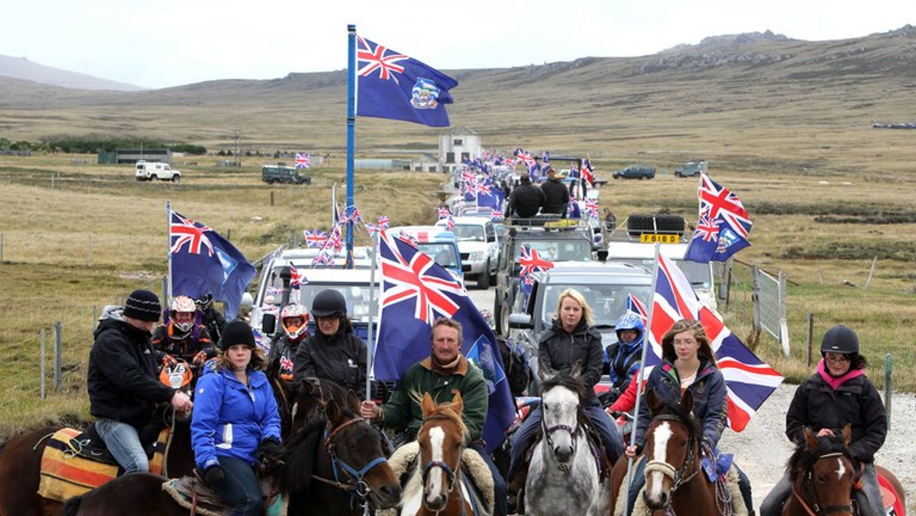 """Islanders take part in the """"Proud to be British"""" parade along Ross Road in Port Stanley, Falkland (Malvinas for Argentina) Islands, on March 10, 2013. Sandy Woodward, who commanded the British navy task force that retook the Falkland Islands in the 1982 war with Argentina, has died aged 81, the defence ministry confirmed."""