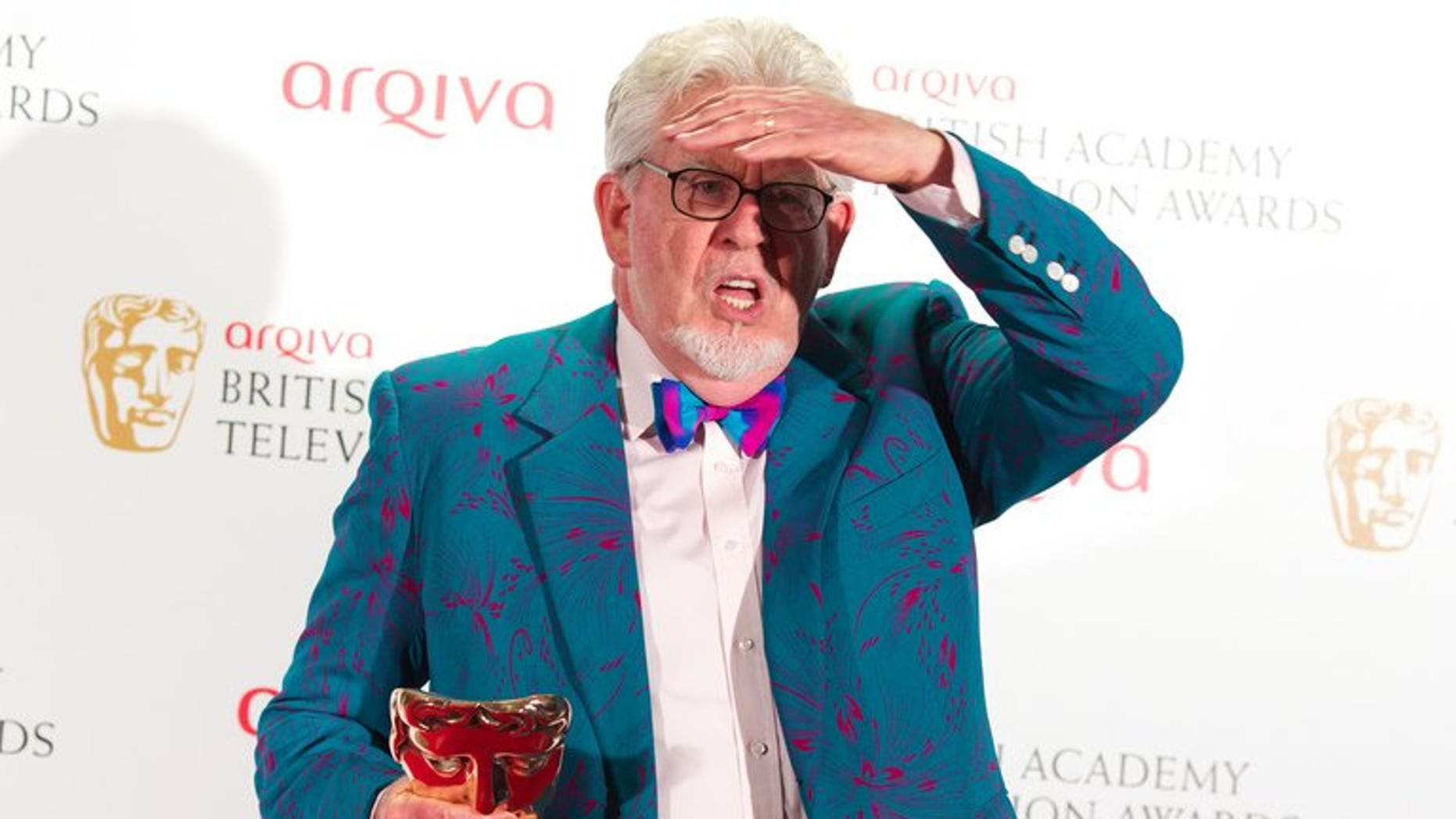Winner of the Bafta Fellowship award, Australian entertainer Rolf Harris poses in front of the winners boards at the British Academy Television Awards at the Royal Festival Hall in London, on May 27, 2012. Harris was re-arrested by police in Britain on Monday over further allegations of sexual offences.