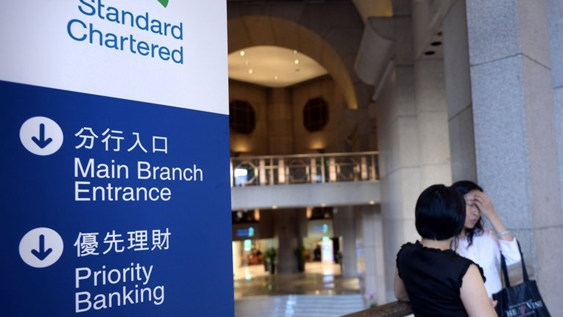 Two women inside a Standard Chartered bank branch in Hong Kong Tuesday. Standard Chartered on Tuesday said its first-half net profit fell 24 percent, with some of its businesses in emerging Asian markets seeing slower growth.