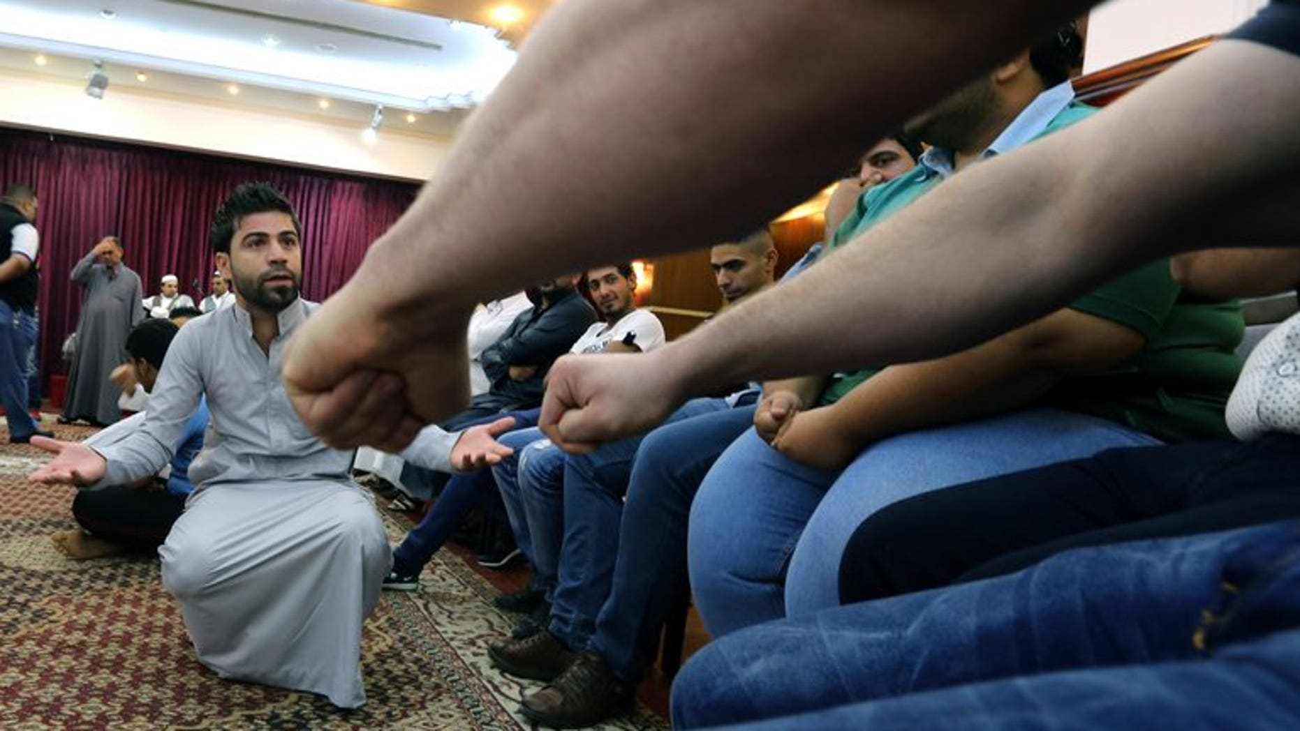 """An Iraqi man takes part in a game of """"Mheibis"""" -- where someone has to guess who is holding a ring in the clenched fist -- in Baghdad, on August 6, 2013. The game of """"Mheibis"""" is wildly popular in Iraq during the holy Muslim fasting month of Ramadan."""