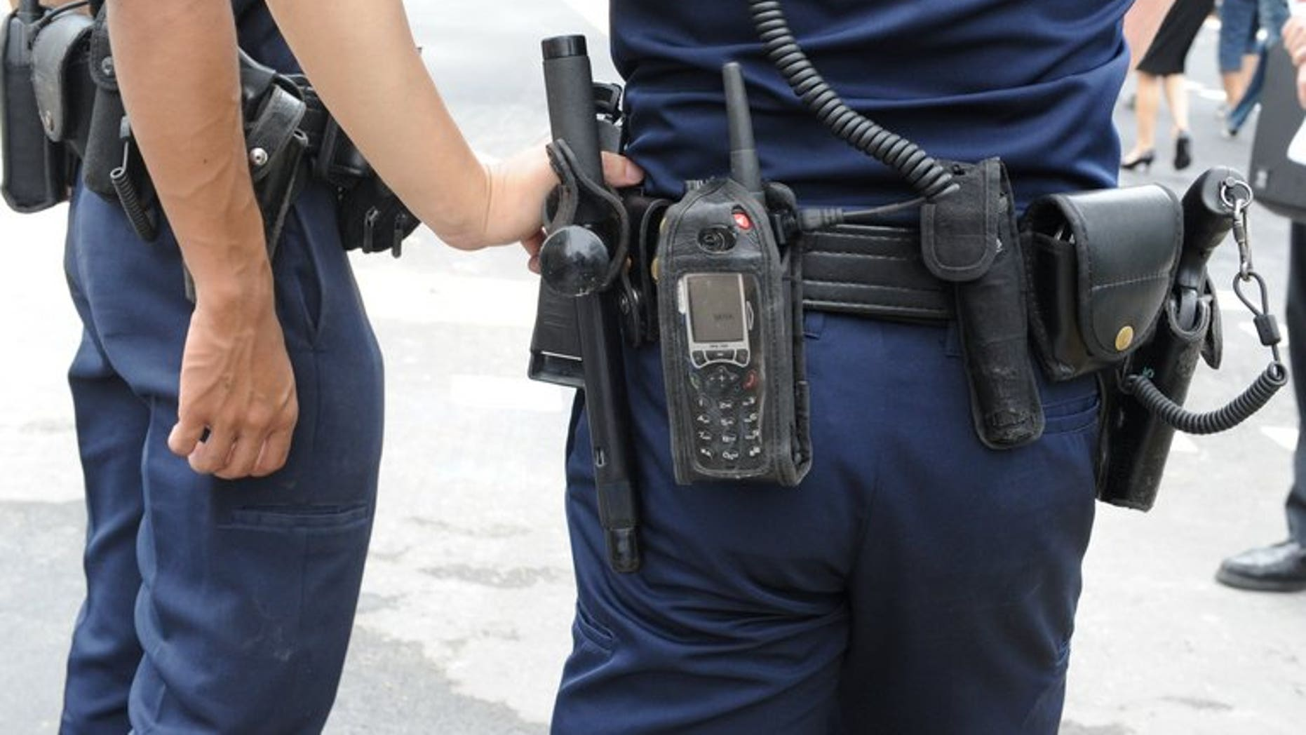 Police officers at work in Singapore on July 18, 2012. A Singapore cartoonist facing jail time over satirical comic strips depicting the city-state's courts as biased had proceedings against him dropped on Tuesday after he made an official apology.