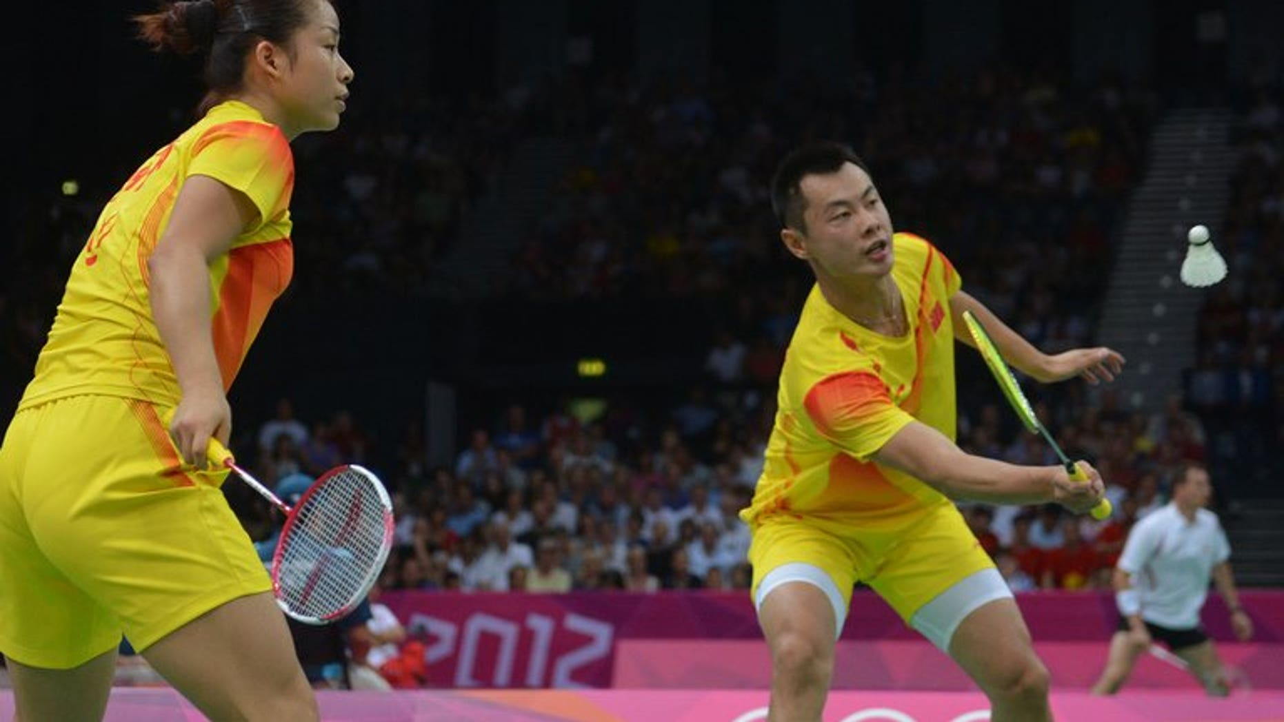 China's Ma Jin (left) watches as Xu Chen returns a shuttlecock as they compete in the mixed doubles badminton event at the 2012 Olympic Games in London, on July 30, 2012. The world's top ranked mixed doubles pair were given a scare in their opening match at the badminton world championships after dropping the first game in an intense clash.